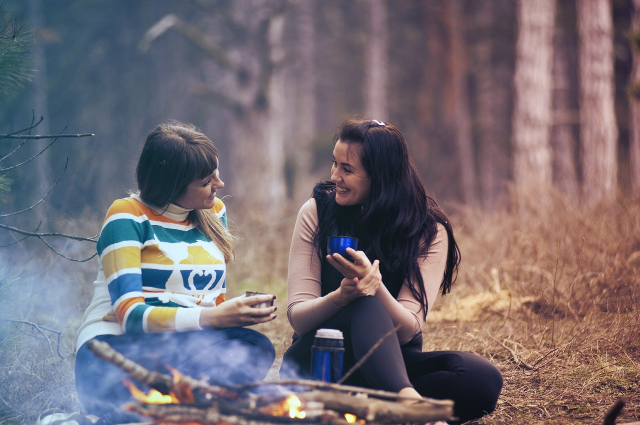 two women at a campfire asking for help as one of them is sick