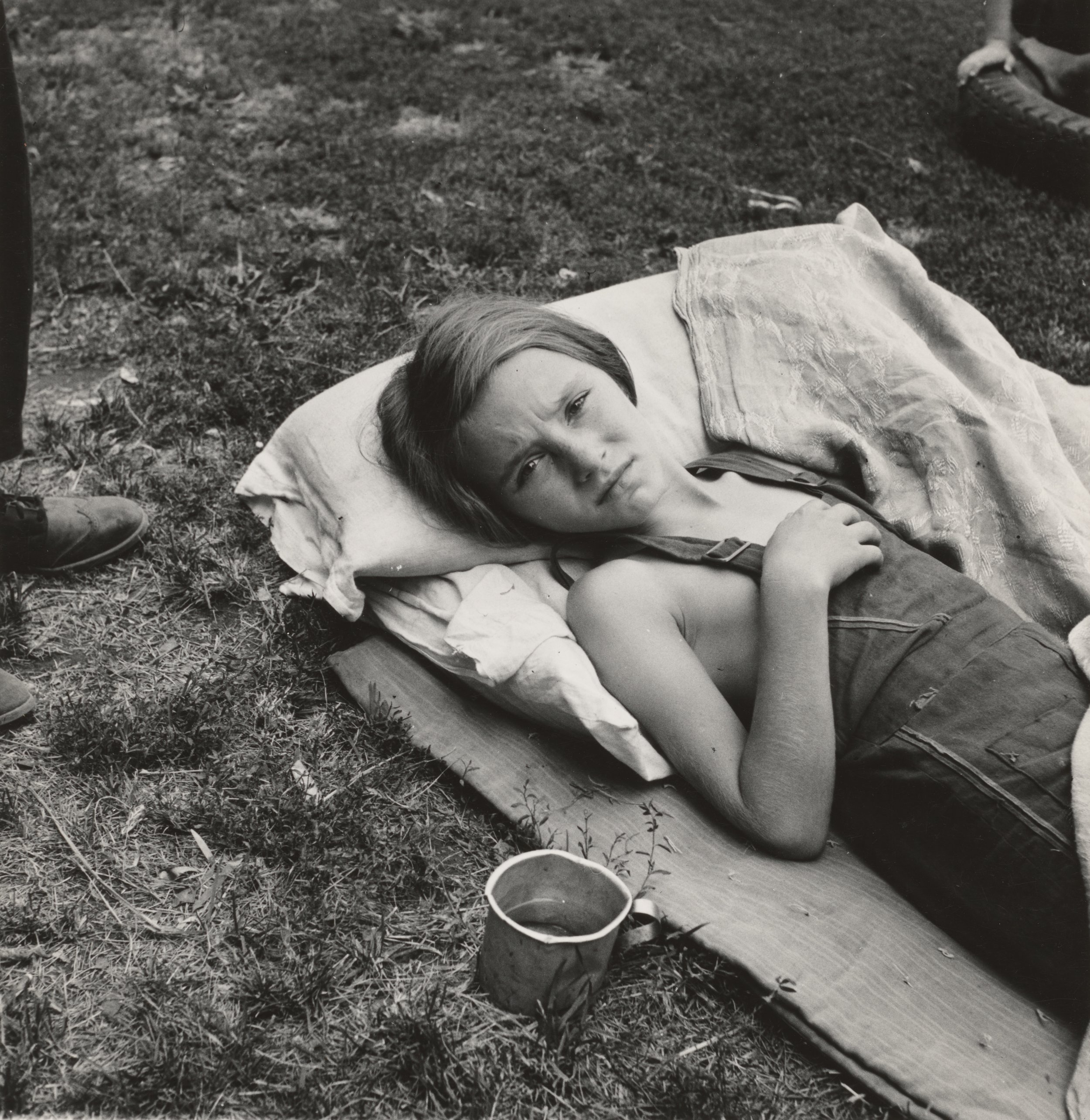 young, sick child laying on blankets and a pillow on the grass next to man standing in boots and a metal can on the ground