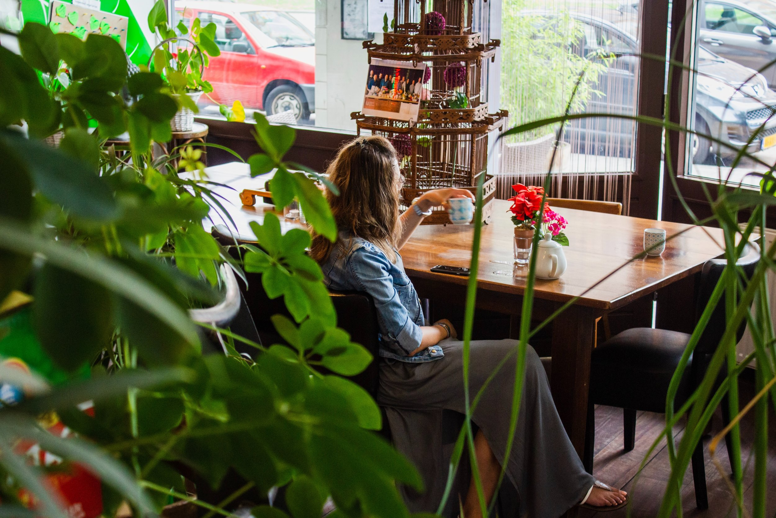 women sitting at a table behind plants, drinking a cup of tea with flowers on the table while thinking anxiously about the future