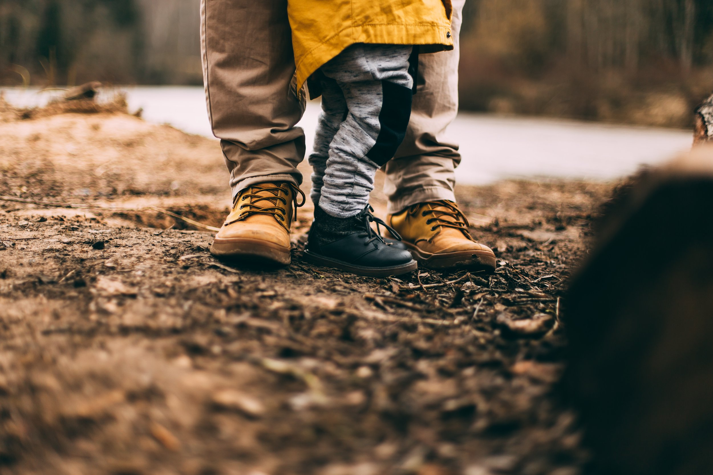 two sets of legs and feet. dad and son wearing boots, standing on the dirt, living in the present moment.