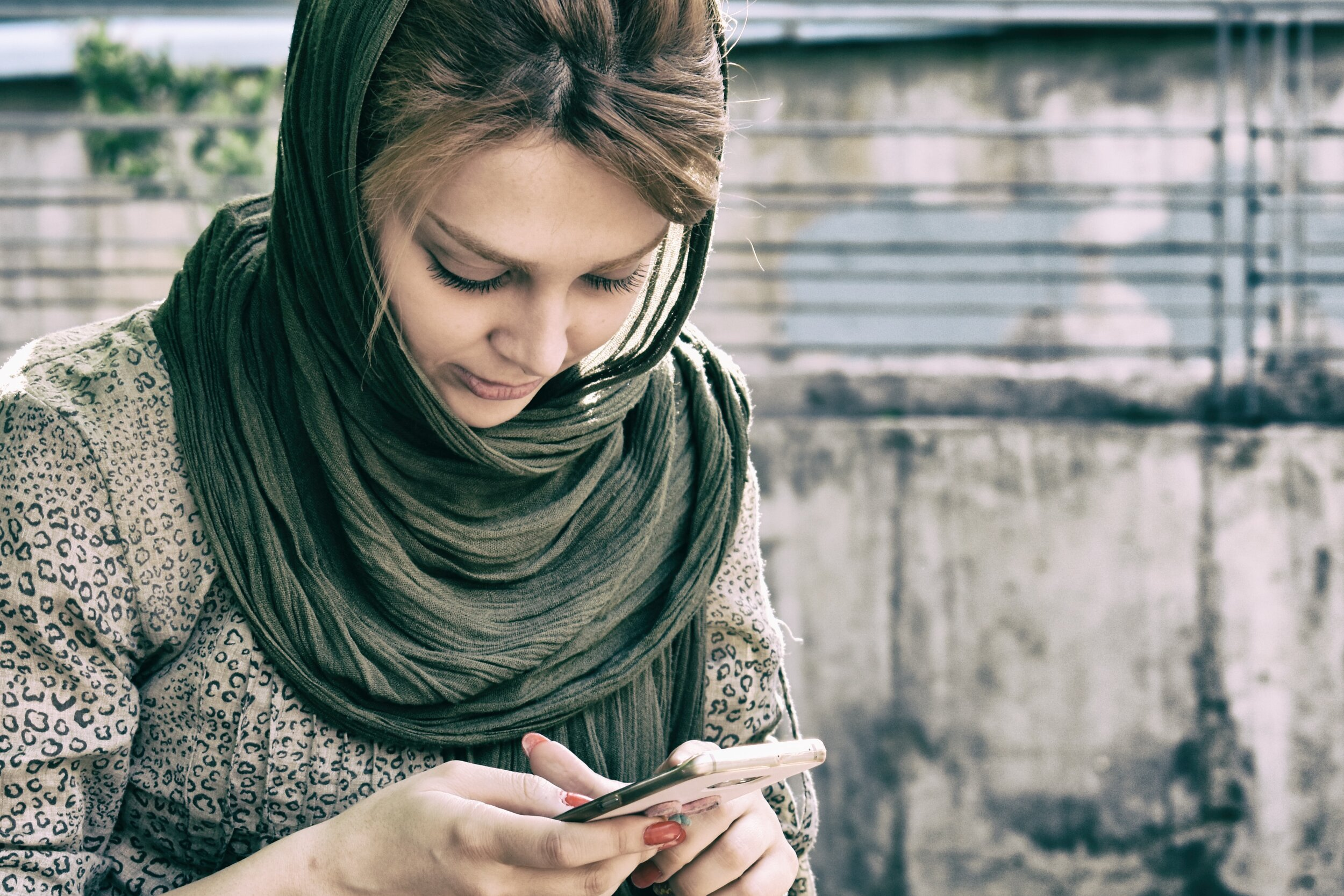 woman wearing hijab texting her friend about her illness