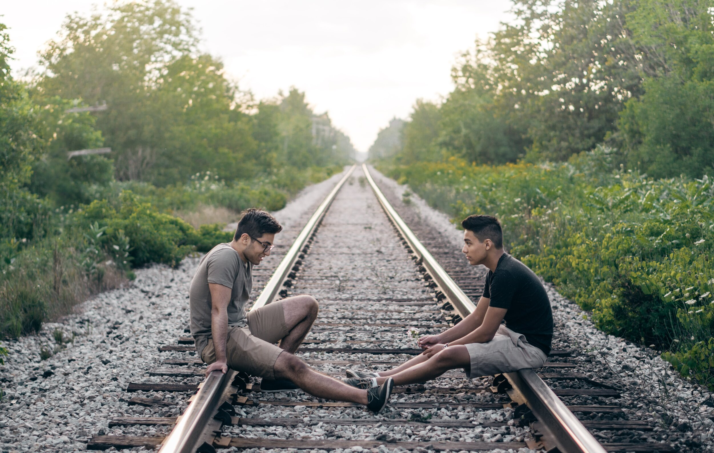 two young men sitting on train tracks having a conversation about mental health and issues