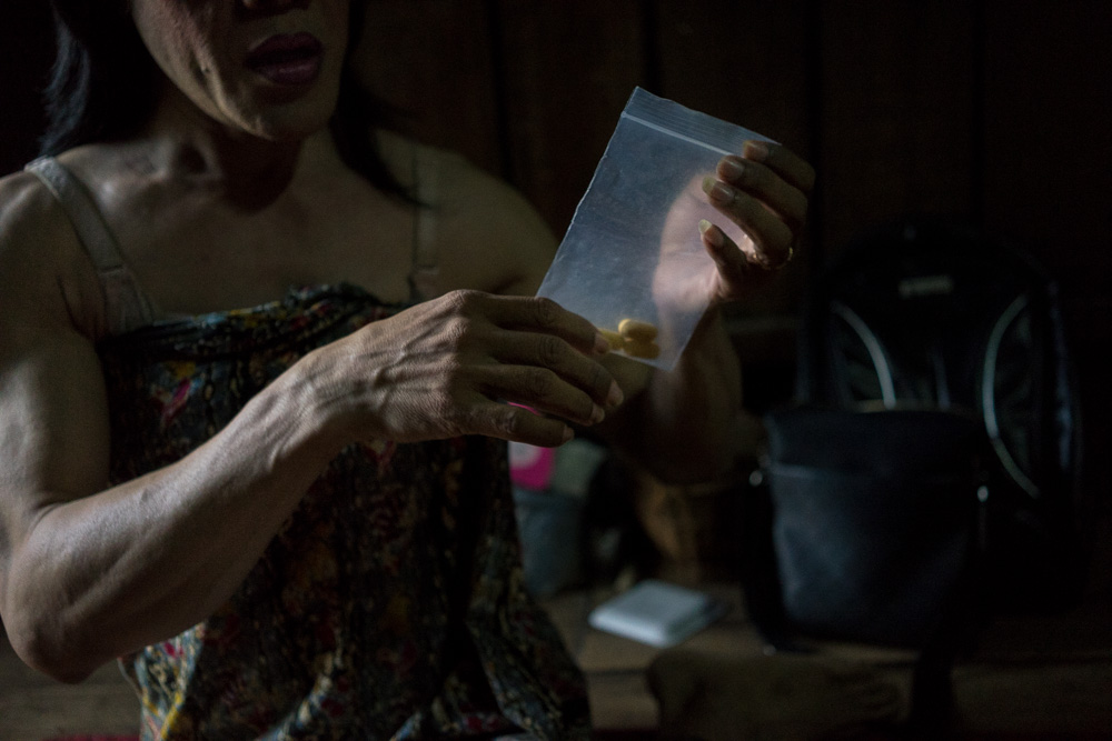 August 08, 2014 - Phnom Penh. Champa takes pills for HIV treatment in her home. Having been herself a sex-worker full time and being HIV positive for more than 12 years, she is very aware of the dangers related to the profession and spends much of her time working as a sex educator. © Thomas Cristofoletti / Ruom