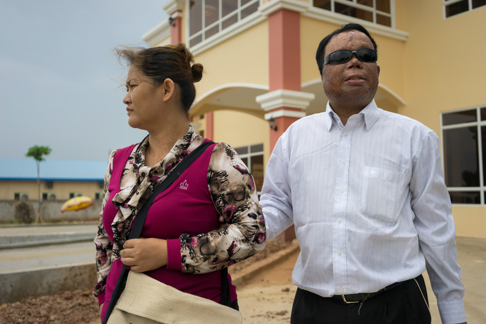 March 21, 2014 - Phnom Penh. Som Bunnarith and his wife pose after the job interview with The National Centre of Disabled Persons. Bunnarith was attacked with acid by her own wife in 2005 and he now has to rely on her in order to survive. © Thomas Cristofoletti / Ruom
