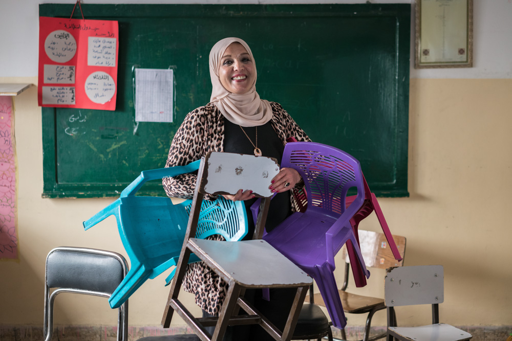 """AMMAN, JORDAN - OCTOBER 1, 2015: Maha al Ashqar is the principal of Khawla Bint Tha'laba Primary Girls School in a suburb of Amman Jordan. The school, which has 356 students, hosts around 65 Syrian students—many of whom have fled violence and destruction in their country to live as refugees in Jordan. Although her school struggles with overcrowding, Al Ashqar is committed to accepting students. She also recounts this powerful anecdote: A few months after school started this year, a Syrian mother arrived at the front gates asking to enroll her daughter. The women at reception apologized, """"There is no way. This school is full."""" The mother was crestfallen. She asked to see the principal and was directed to Al Ashqar. And as she has done so many times before, the principal told the mother that, of course, she would enroll her daughter. But she had one request, """"Please bring a chair."""" """"This touched me,"""" Al Ashqar explains. """"I saw the tears of many mothers, and it was impossible to tell them that we had no room, to try somewhere else. I told them, just bring a chair with you, even if it's a small plastic chair, and we will make do."""" © Thomas Cristofoletti / Ruom for USAID"""