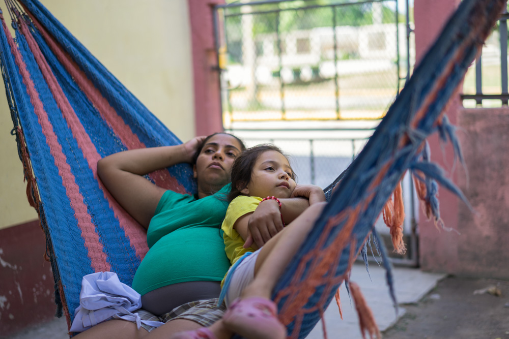 July 01, 2015 - San Pedro Sula (Honduras). Odalis Fernanda Triminio Leiva, 26, helps her daugther Fergie with her homework. Odalys runs a small pastry shop out of her home in the Rio Blanco community. She started the business after receiving training from USAID's Metas workforce development program. She bakes cakes and donuts -- her specialty is tres leches, and finds customers by promoting her business on social networks and among her friends. The small business is helping bring in money to support her family -- her husband, David, 33, their daughter, Fergie, 7, and a second child yet to be born. © Thomas Cristofoletti / Ruom for USAID