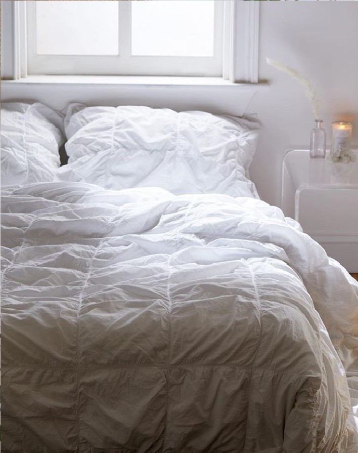 Lighten Your Sheets - If you currently have dark, cool colored sheets or comforters, swap them out with lighter, pastel colored ones or simply an all-white bedspread. Not only will this brighten up your room, but the lighter the sheets, the cooler the temperature in your bed.Urban Outfitters Home
