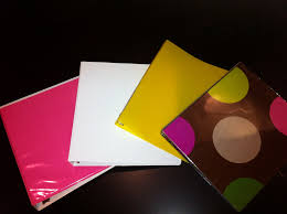 4 three ring binders. one pink, one white, one yellow, and one with polka dots