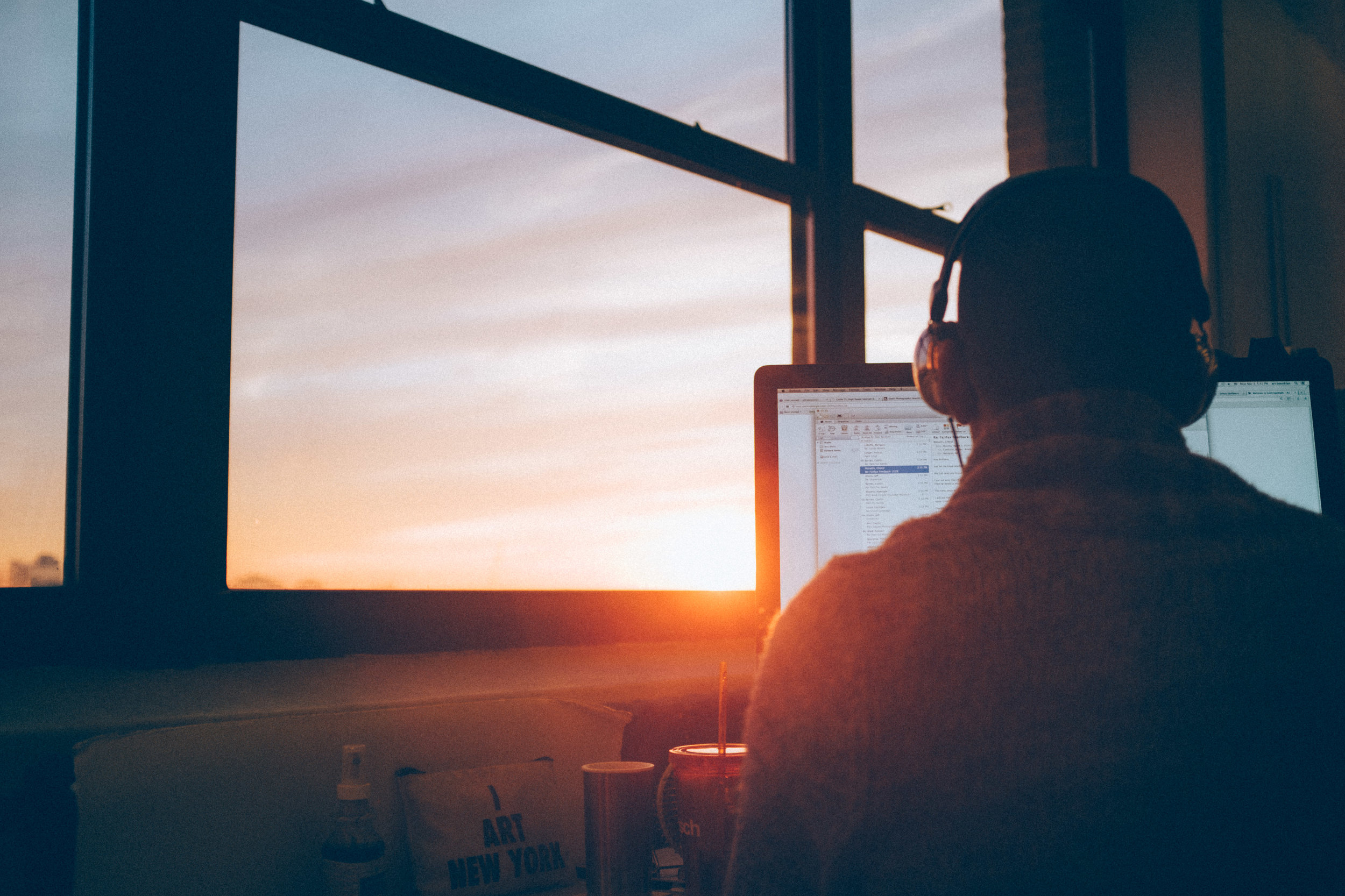 a man sits at a desk in front of a window. The sun is setting and the man is wearing headphones looking at a computer screen. He appears to be dictating words to the screen