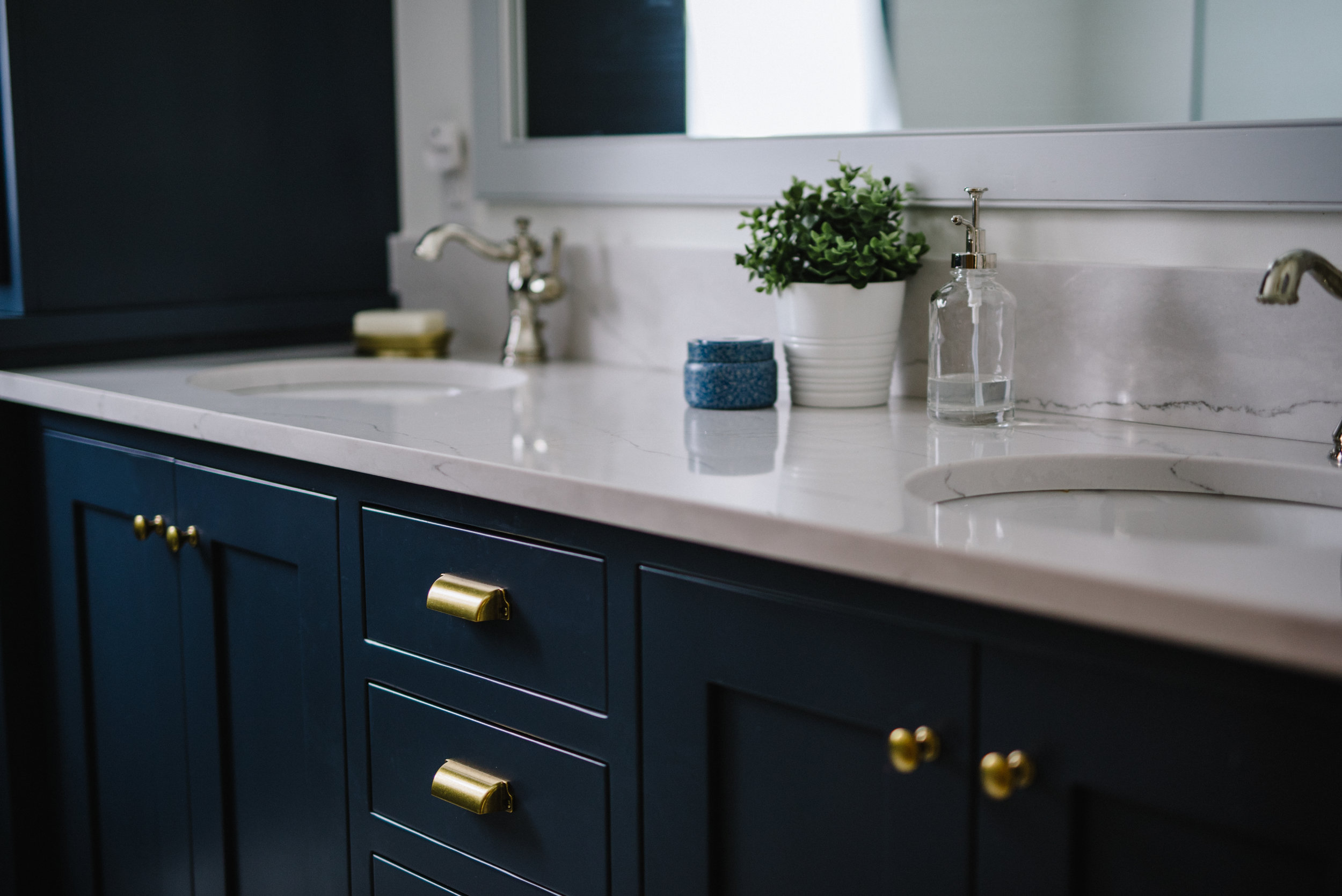 Inky blue cabinets with  Ella cambria quartz counters ,  Delta cassidy faucets in Brilliance Polished Nicke l,  hardware by Martha stewart at home depot.  custom cabinets & Mirror by brian stoll, jonesville, MI. Photos by Rachel Cuthbert Photography.