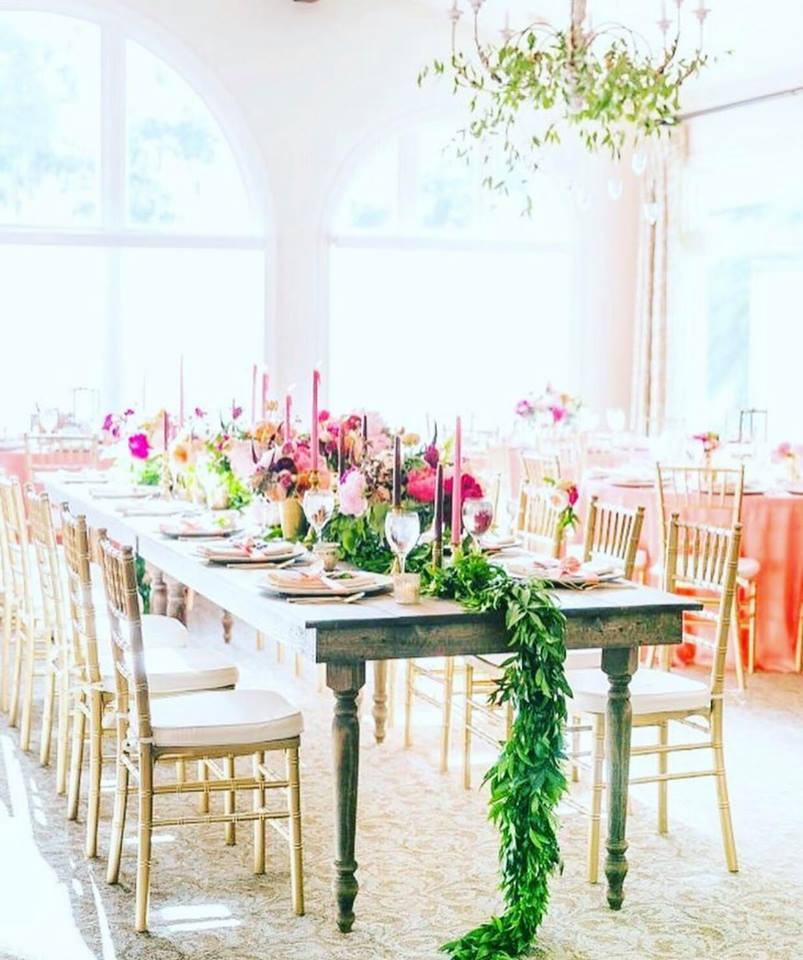 This table uses pretty hues of pinks offset by a green garland - image source / pinterest