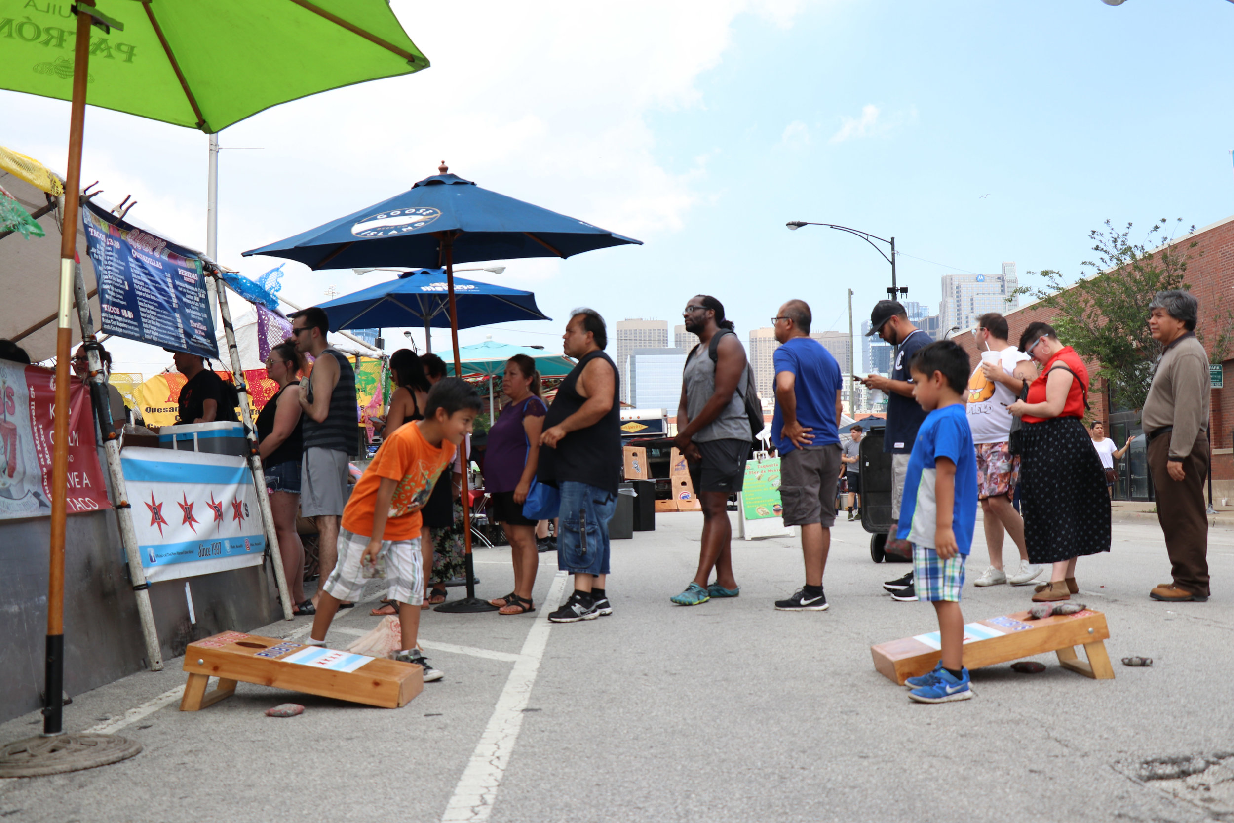 Children entertain themselves with a game of cornhole, as their parents wait in line to get seats at a popular food stall. Maxwell Street Market, South Desplaines Street. Chicago, 2018. (Vangmayi Parakala/MEDILL)