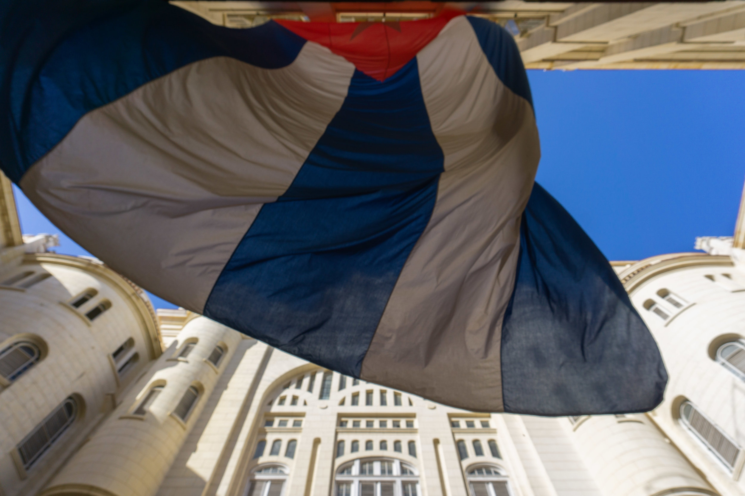 A huge Cuban flag flutters in the courtyard of the Museum of the Revolution. Havana, 2018. (Vangmayi Parakala/MEDILL)