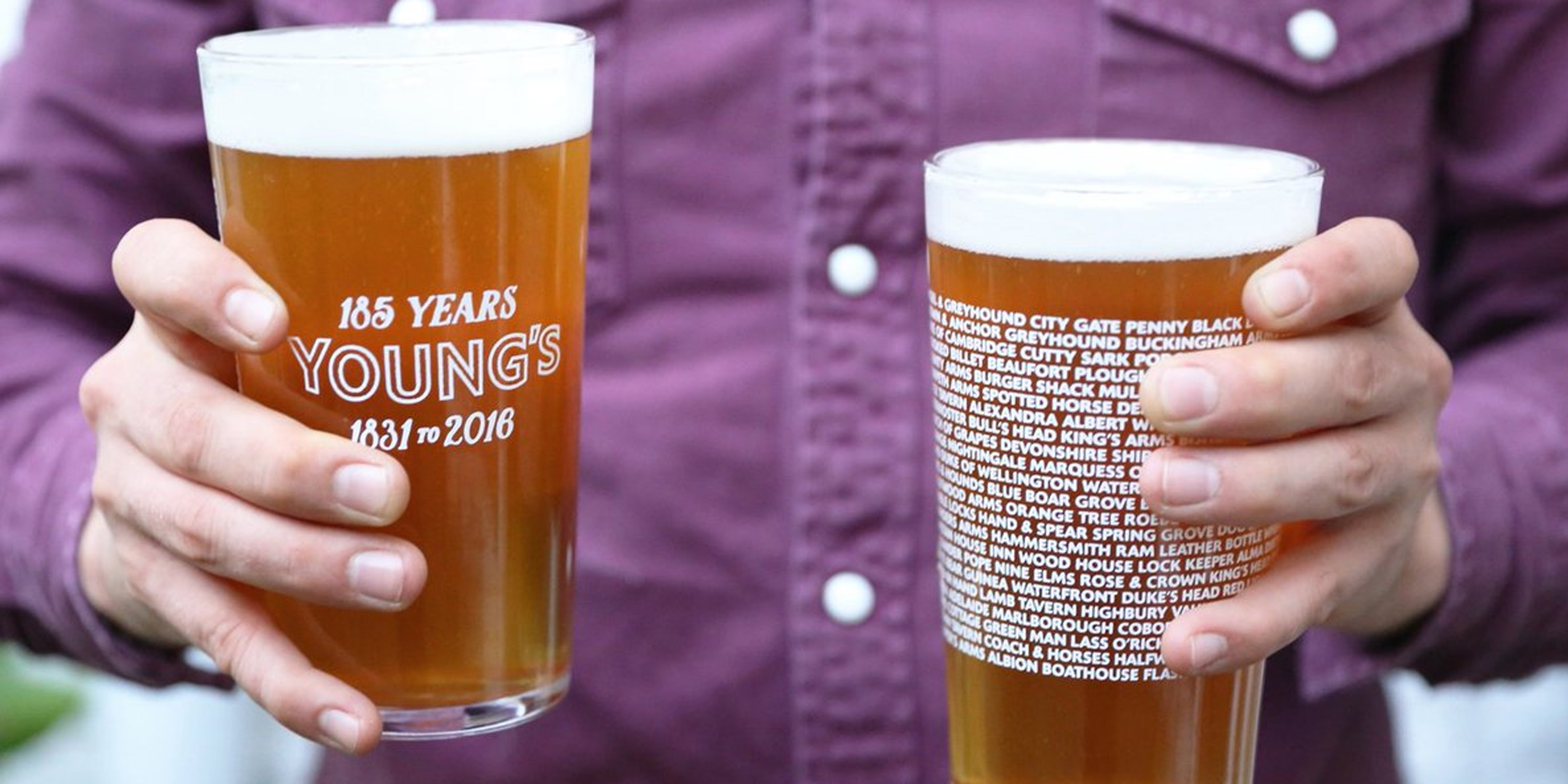 Close-up of man holding two Young's Day custom branded commemorative pint glass