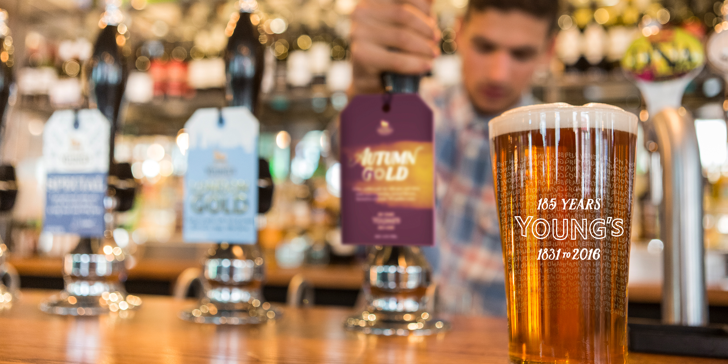 Young's Day commemorative pint glass on bar with Autumn Gold beermat in the background on bar tap