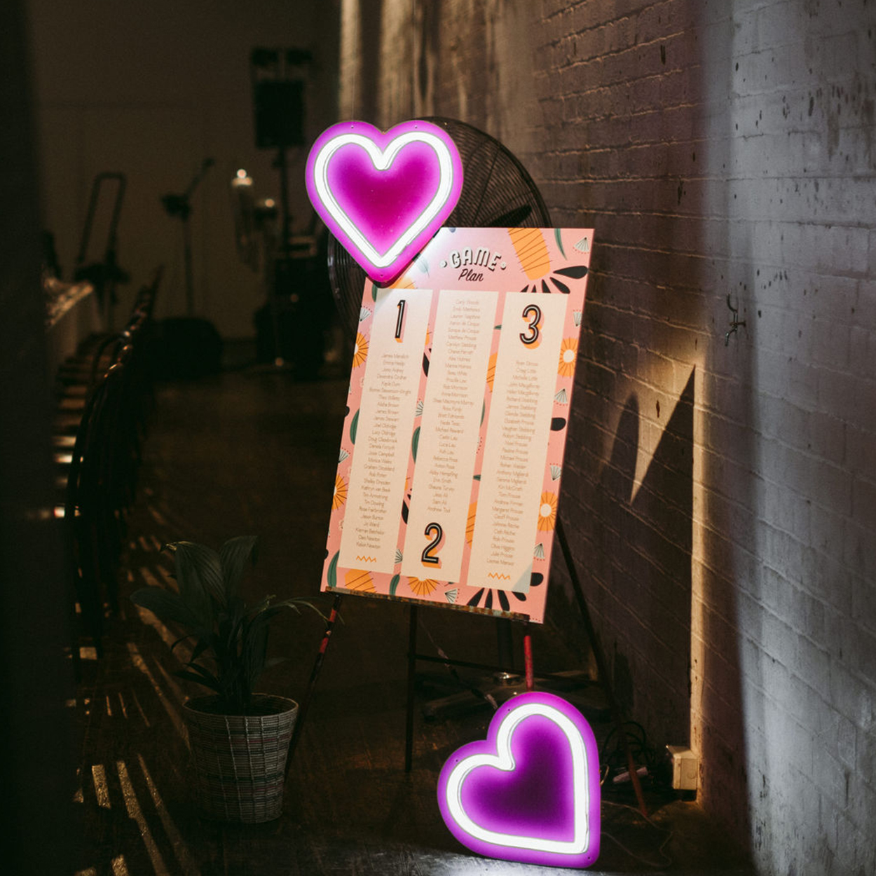 Wedding seating chart with custom typography and bespoke illustration with  neon signage against wall