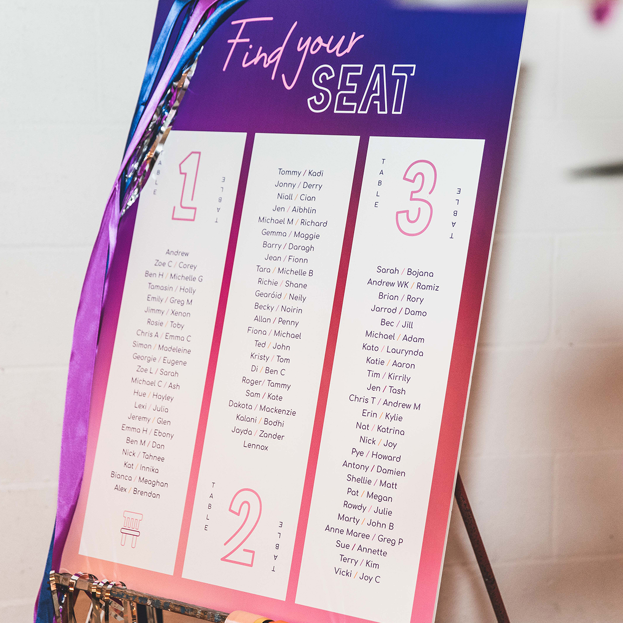 Wedding seating chart with custom typography against wall with tinsel and ribbons