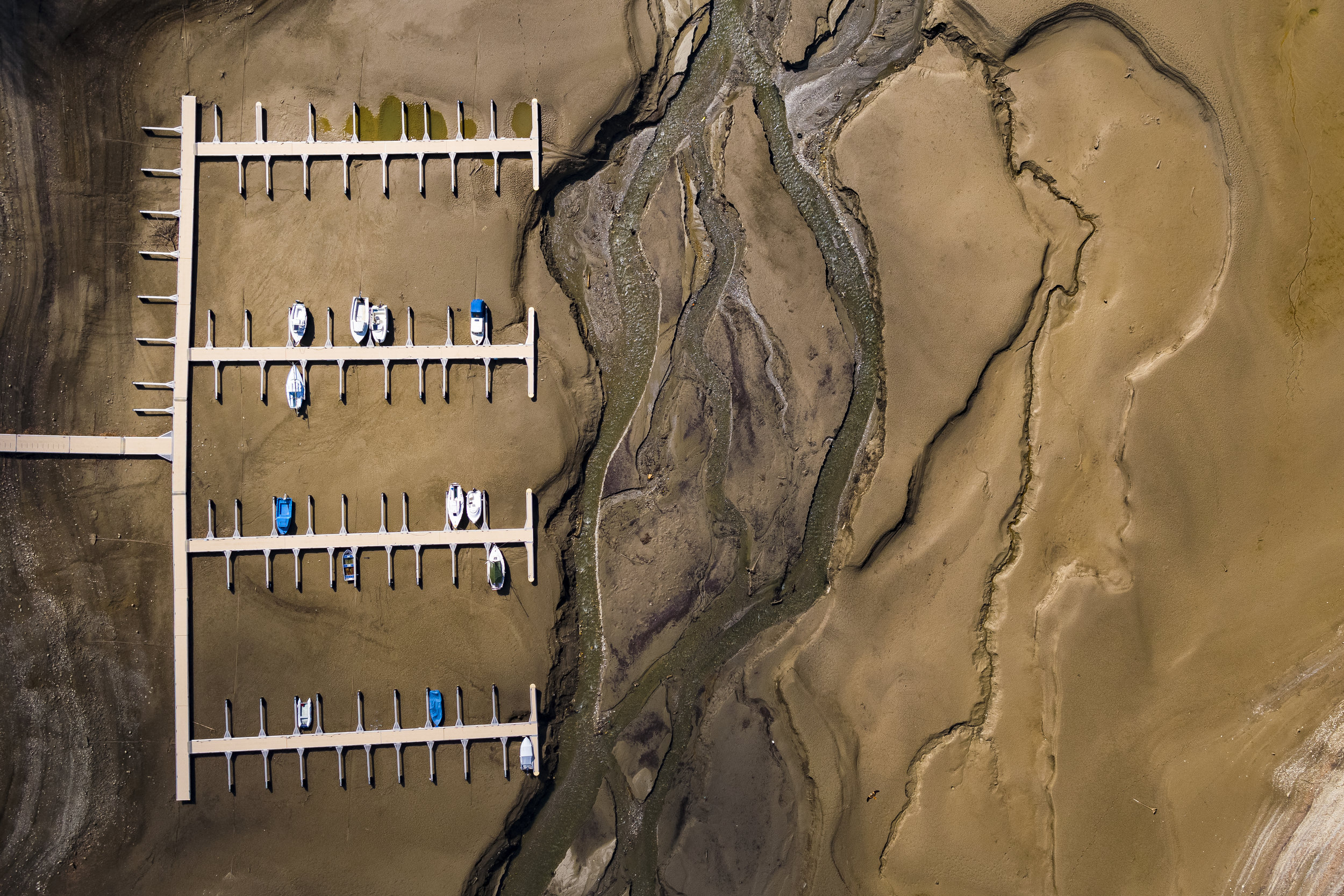 Stranded boats are pictured on the dried out shores of the Lake of Gruyere in la Roche near Bulle, Switzerland, Wednesday, March 14, 2018. The level of the artificial reservoir lake is progressively being brought down by 15 to 20m, planning for the upcoming melting of the heavy snowfalls accumulated on the surrounding mountains. (KEYSTONE/Valentin Flauraud)