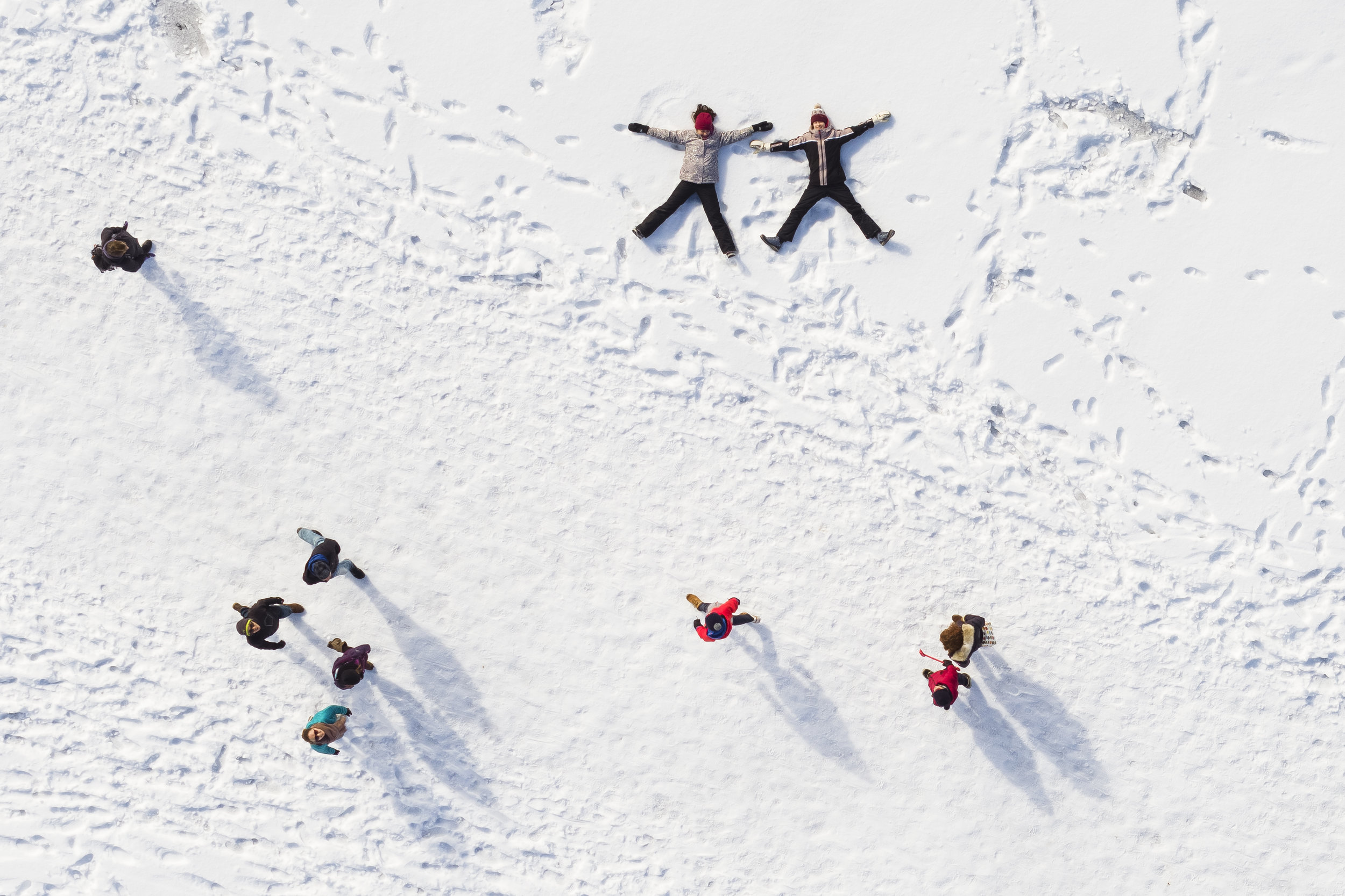 """Children play in the snow as people walk by on the frozen lake """"Lac de Joux"""" after a series of cold days in Le Pont, Western Switzerland, Sunday, March 4, 2018. (KEYSTONE/Valentin Flauraud)"""