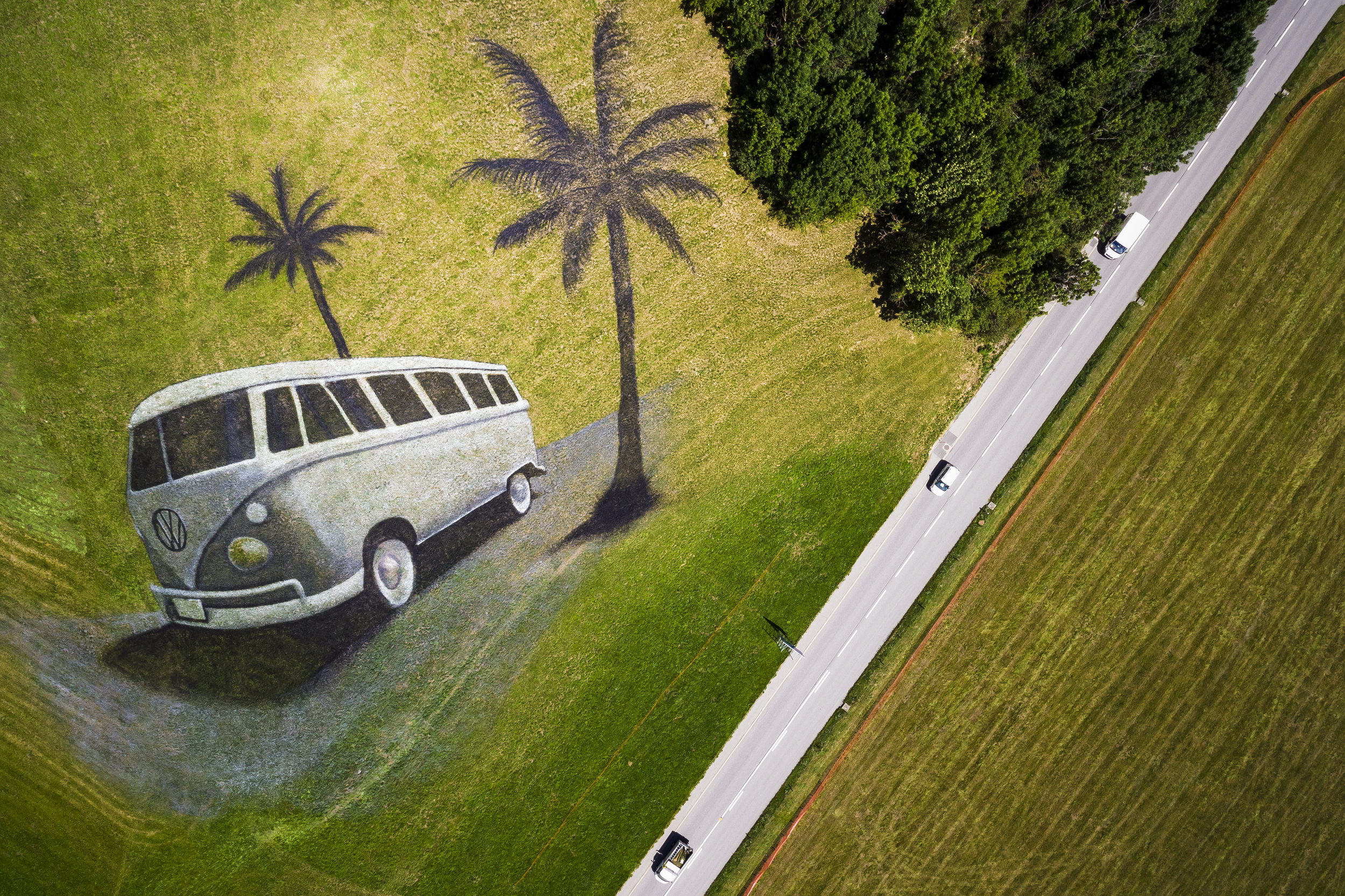 A landart painting by French artist Saype, depicting a Volkswagen (VW) bus, is pictured on a hill in Chateau d'Oex, Switzerland, Wednesday August 23, 2017. The artwork covering approximately 4200 square meters was produced with over 400 liters of biodegradable paint made from natural pigments, water and a milk protein and is part of the upcoming 20th international VW festival. (KEYSTONE/Valentin Flauraud)