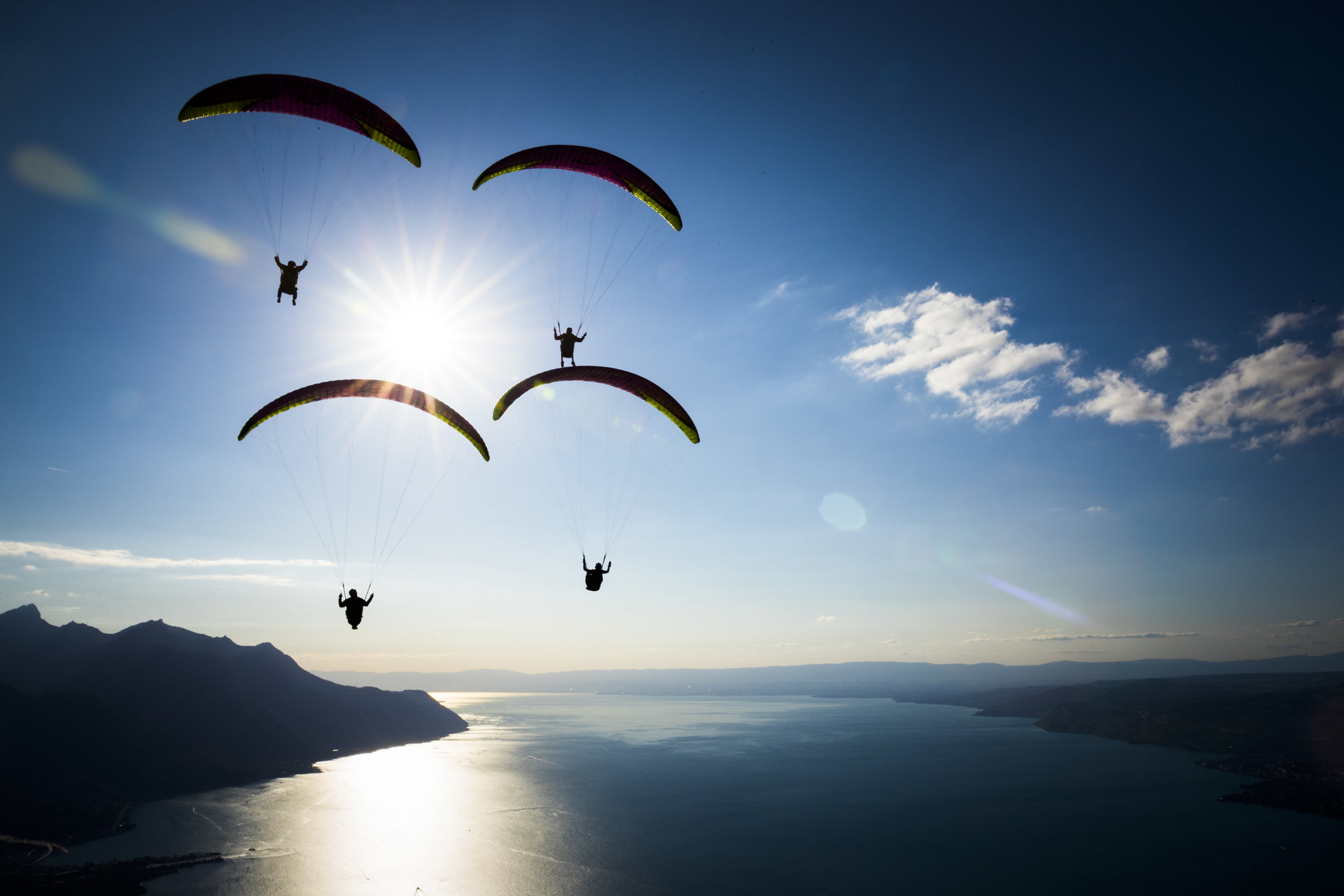 """Paragliders fly past the sun towards the landing area of the """"Acro Show"""" above Lake Geneva in Villeneuve, Sunday August 20, 2017. (KEYSTONE/Valentin Flauraud)"""