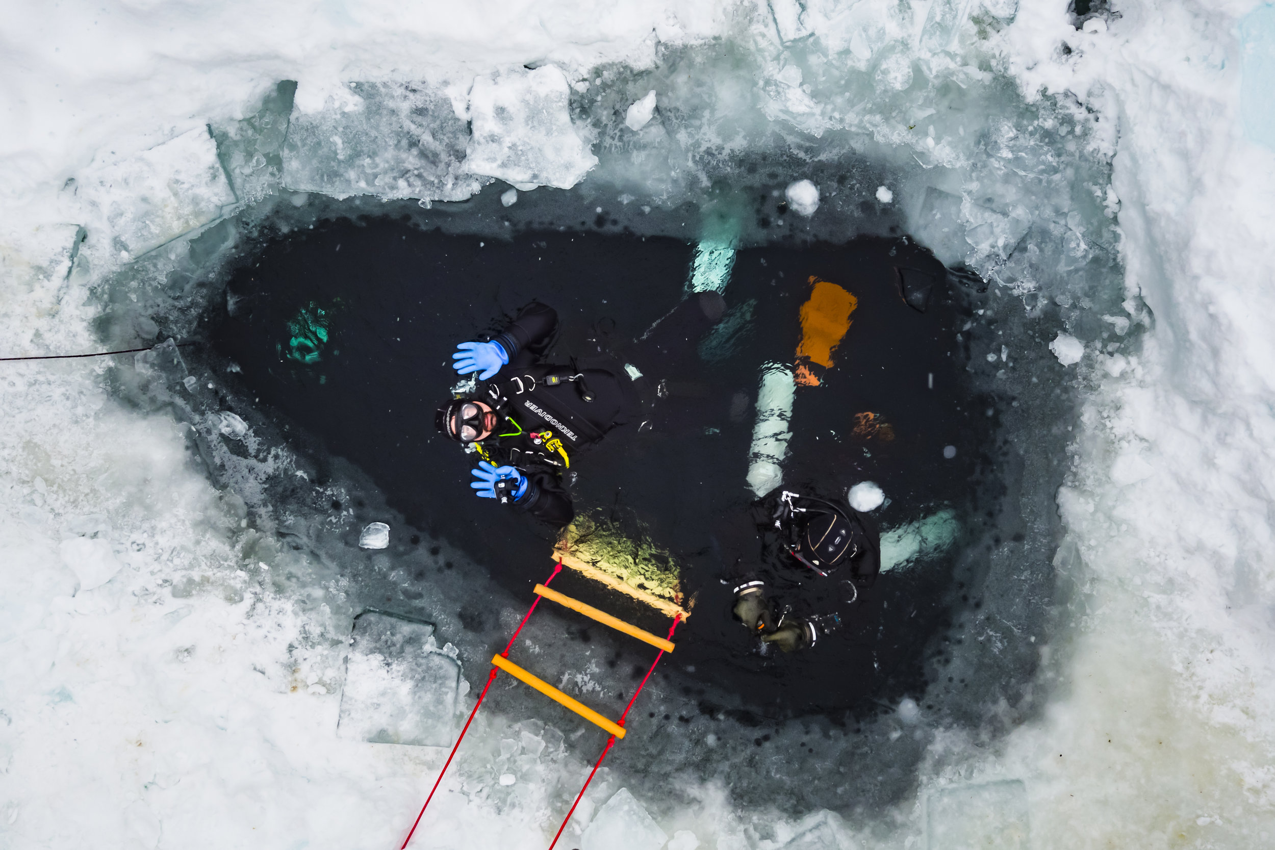 Divers enter the freezing water of the alpine Lioson Lake, 1900m, in Ormont-Dessous, Switzerland, Saturday, February 10, 2018. After a one hour hike in snow shoes the group of 18 divers enjoyed dives down to 15m depth below a layer of ice of almost 1m thickness. (KEYSTONE/Valentin Flauraud)