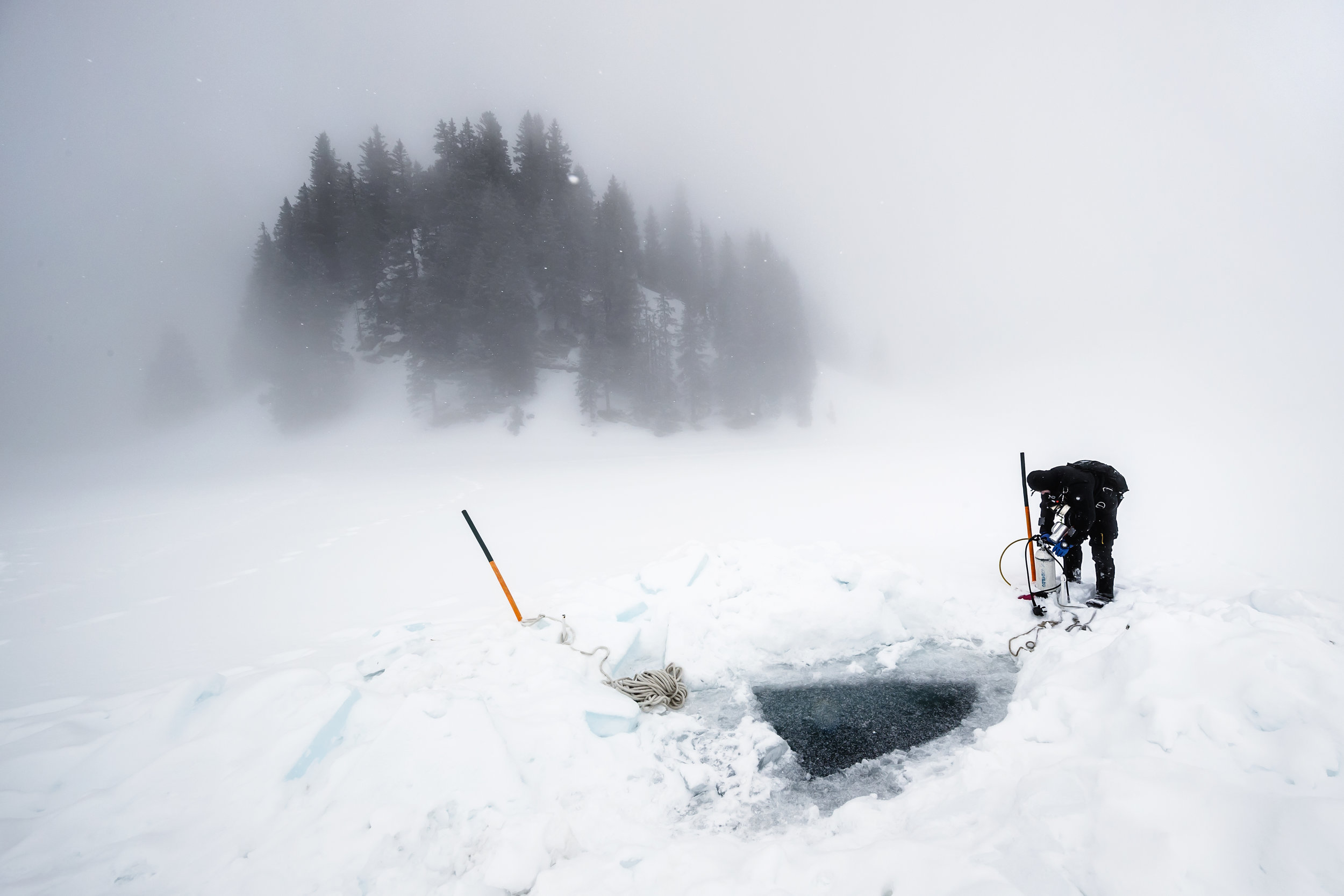 A diver prepares his equipment before diving in the freezing water of the alpine Lioson Lake, 1900m, in Ormont-Dessous, Switzerland, Saturday, February 10, 2018. After a one hour hike in snow shoes the group of 18 divers enjoyed dives down to 15m depth below a layer of ice of almost 1m thickness. (KEYSTONE/Valentin Flauraud)