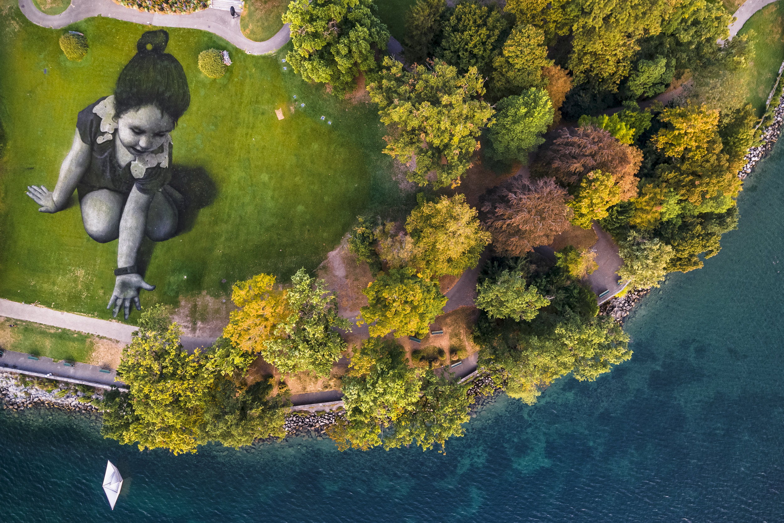 """A giant landart painting entitled """"Message From Future"""" by French artist Saype, is pictured in the park """"La Perle du Lac"""" in Geneva, Switzerland, Sunday September 16, 2018. The artwork covering 5000 square meters was produced with biodegradable paints made from natural pigments. The artist called the little girl """"Future"""" as a symbol of the generations from the future and the small origami boats that she drops into Lake Geneva aims to represent a message of hope sent to the world. (KEYSTONE/Valentin Flauraud)"""