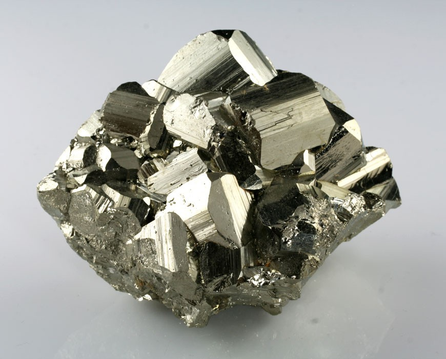 "Pyrite, also known as ""fools gold,"" is a widespread and common iron sulfide that is pale brassy yellow in coloration and may contain trace amounts of silver, gold, cobalt and nickel. Pyrite can come in many different appearances. Its crystal aggregates may be large and beautiful, coming in perfect cubes or penetration twins or a number of other wonderful and bizarre crystal forms. Smaller aggregates are pleasing, as well, in that that tend to glisten and sparkle in the light. Pyrite got its name from the greek phrase ""pyrite lithos,"" which means ""stone which strikes fire."" This is because striking it against metal or a hard surface can create sparks. Pyrite provided human society with a great gift: one of its earliest methods of creating flame. Although pyrite is no longer considered to be of high monetary value itself, it retains value as an indicator of the presence of other minerals or metal ores of significant value. In the past, however, it was used for a variety of reasons, including divination, the tricking of naïve prospectors by dishonest mine owners, decorations/ornaments and jewellery, and as a source of sulfur for the production of sulfuric acid during World War II.  Pyrite resonates with the energy of the earth and fire. It is regarded as a mineral of action, will and vitality, and it is said to have the ability to tap into one's potential and and empower him or her with the knowledge and awareness that wealth can be generated through one's own power. It is believed to promote confidence, persistence and defense against negative energies and pollutants. It may bring out a person's boldness and assertiveness when protecting or standing up for other people, the planet, and/or issues within the community. It is said to stimulate the second and third chakras, enhancing the ability to distinguish between facades and what is real, as well as enhancing will power.  Physically, pyrite is believed to activate nourishing energies within the body by drawing on universal energies. It may be good to have around in cases where no resolution has been found, as it is claimed to bring out the cause or root of disease for examination. It is also believed to assist the immune system in the fight against disease and infection by shielding the body from contagious pathogens and pollutants. It has also been used to fight inflammation and fever. It may strengthen the circulatory and respiratory systems by increasing oxygen supply to the blood and alleviating bronchitis and asthma. Wearers also claim that pyrite can prevent and repair DNA damage, assist in bone treatments, combat impotence and infertility in males, and promote healthy endocrine function."