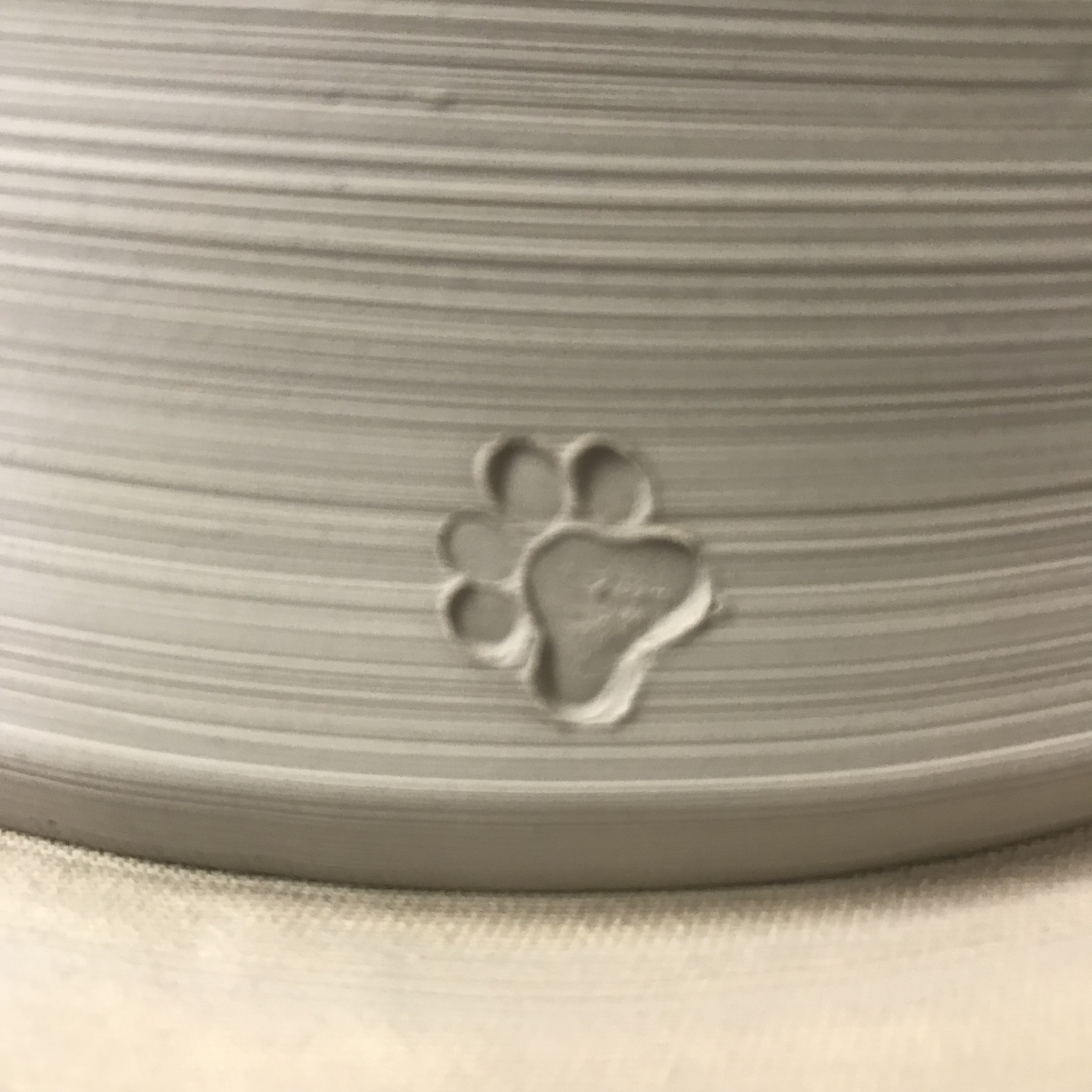 3 paw print stamped on leather hard pot.jpg