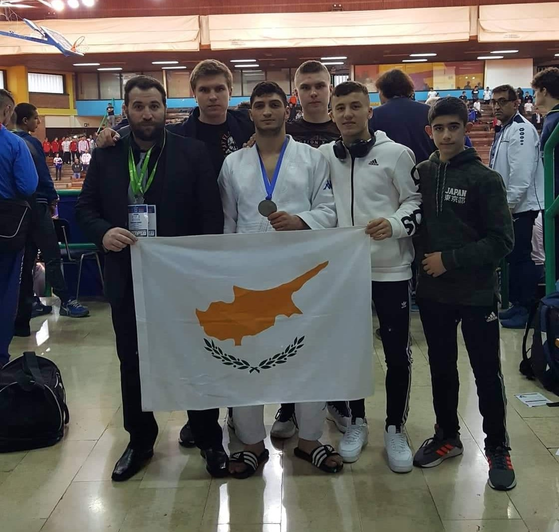 Silver medalist Panagiotis Shakkos pictured with coach Marinos Piponas and other members of the team proudly flying the Cypriot flag