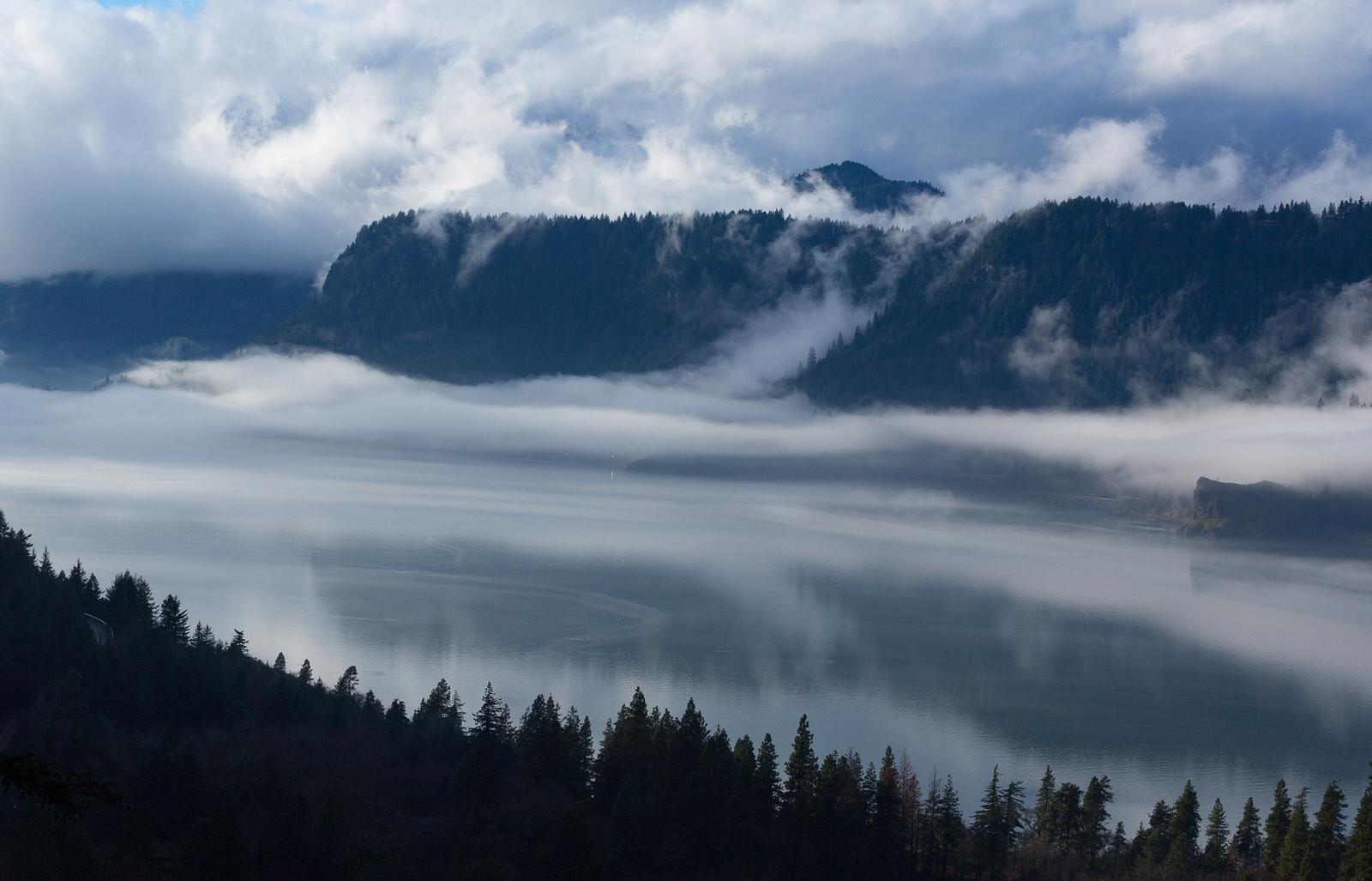 Fog flows over a calm Columbia River