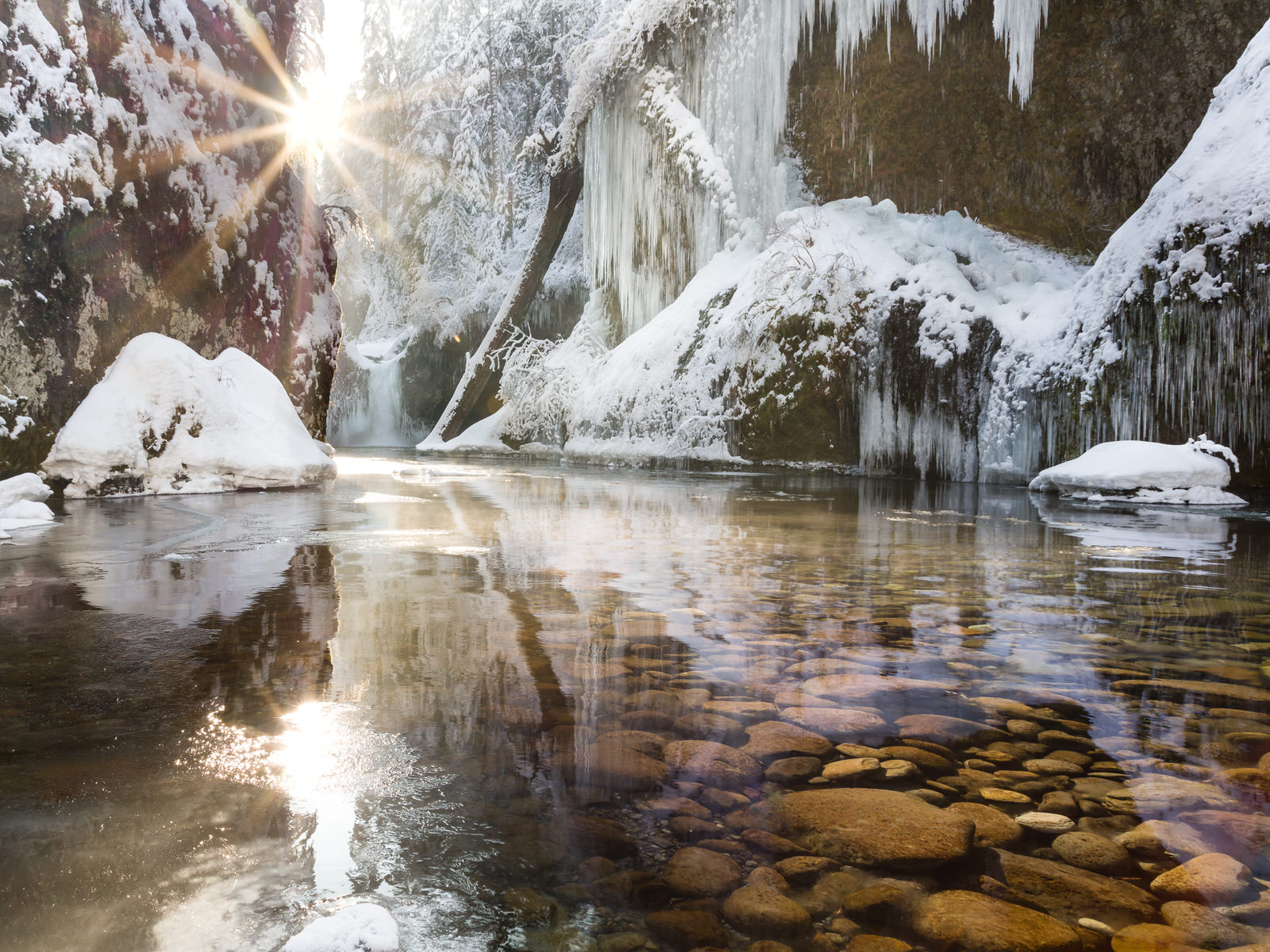 Sunburst behind frozen Punchbowl Falls