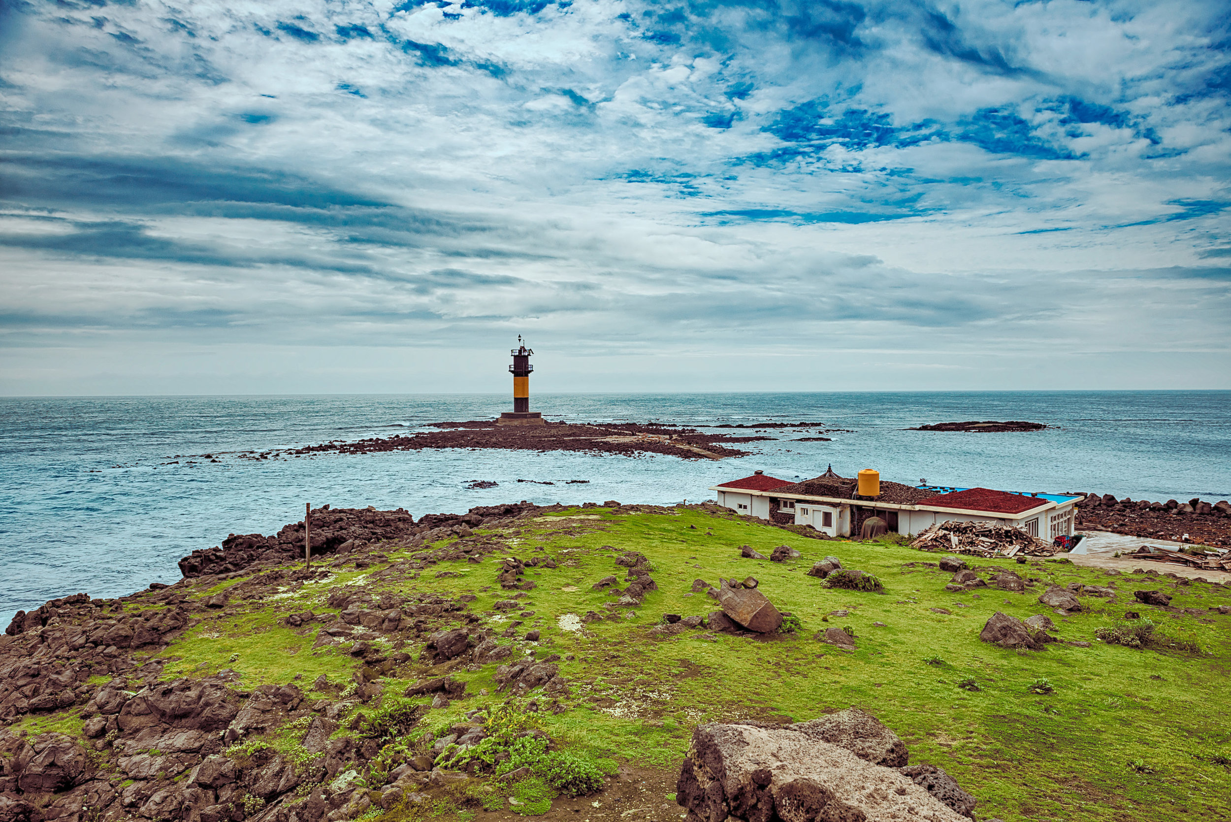 The lighthouse on the edge of Biyang Island (비양도) being surrounded by ocean during high tide.