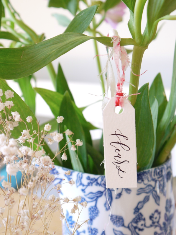 Vases of flowers - Why not tie a hand-lettered label to a plant stem or around the handle of a jug of flowers to make them sing even more. One or two words written on will be enough. Alternatively, fill an empty jam jar with flowers cut from the garden, wind some twine several times around the rim and then add on a gift tag. It's the small changes that make the biggest differences here.