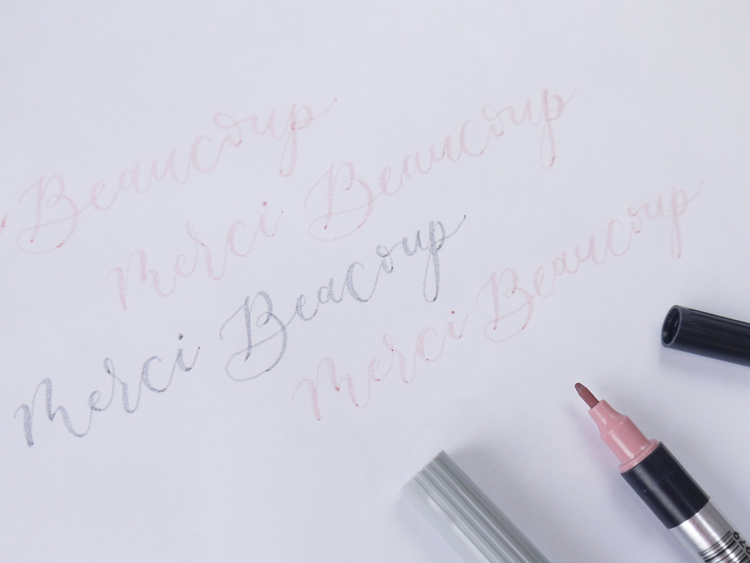 The finish on layout paper is much smoother but you'll need to lift the pen at the end of each stroke otherwise you'll get dark dots which you can see on grey and last pink lettering.