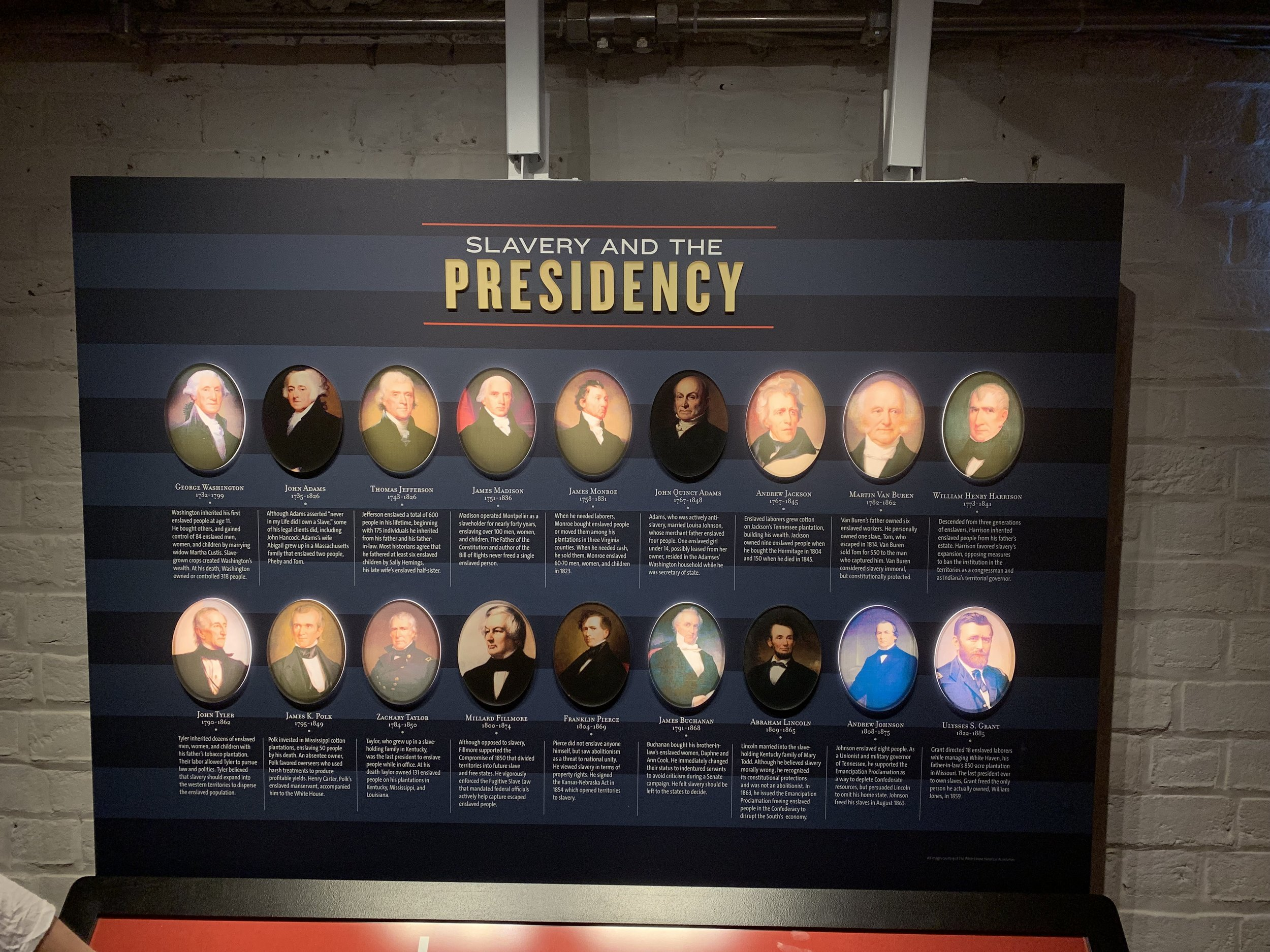 "Thirteen of the first eighteen presidents were slave holders. The backlit portraits indicate slave owning presidents. This graphic is from ""The Mere Distinction of Colour"" exhibition in the cellar of the Montpelier. Created by  Proun Design , The Montpelier Foundation. Photo by Renée Ater, August 2019."