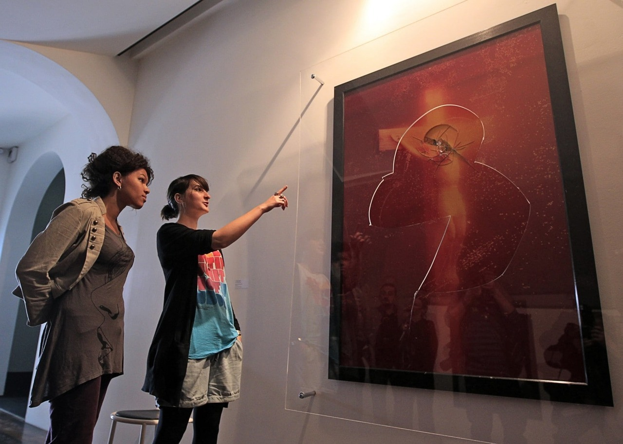 "Andres Serrano's ""Piss Christ"" (1987) after it was attacked in April 2011 while on view at the Collection Lambert in Avignon, France. As confirmed by surveillance footage,  three vandals aided by ""a hammer and an object like a screwdriver or pickaxe,"" according to museum officials, attacked the piece, shattering glass and puncturing the print. No arrests were made; the work remained on view as it was, ""so the public can appreciate for themselves the violence of the acts."""