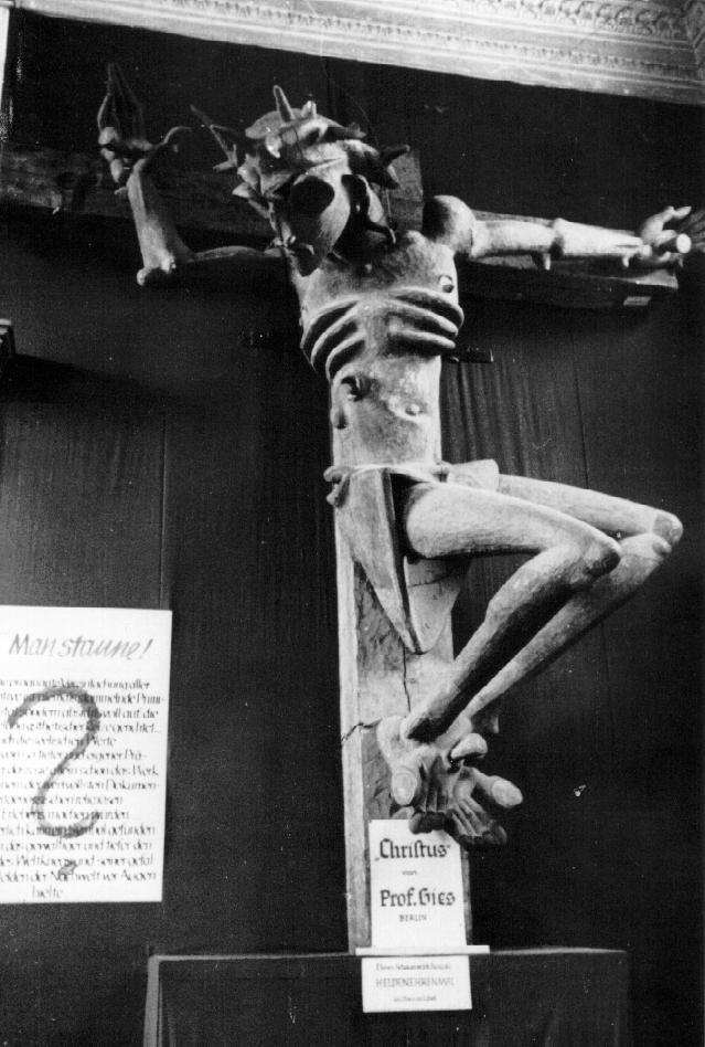 """Ludwig Gies,""""Kruzifixus (Crucified Christ)"""" 1921 / church parishioners, Nazis  This Expressionistic wood sculpture, initially conceived as part of a proposed WWI war memorial, was offered to Germany's Lubeck cathedral in 1921. Once installed on a trial run, however, the work immediately provoked controversy among both the parish and the press. On March 3, 1922, unidentified parties entered the cathedral and sawed off the sculpture's head, which was later found floating in a nearby mill-pond.  The piece was eventually repaired and moved to the Stettin Museum - until it was confiscated by the Nazis in 1937, who then included """"Kruzifixus"""" in its Munich exhibition of""""Degenerate Art"""" (as shown in the above photo). At the conclusion of the exhibition, the work was destroyed beyond repair."""