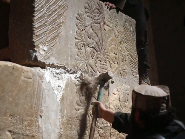 """""""An image grab taken from a video made available by Jihadist media outlet Welayat Nineveh on April 11, 2015, allegedly shows members of ISIL destroying a stone slab with a sledgehammer at what they said was the ancient Assyrian city of Nimrud in northern Iraq."""""""