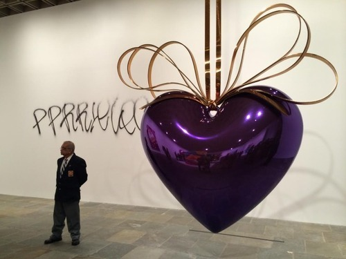 Jeff Koons retrospective / spray paint   On October 18, 2014, a man later identified as Christopher Johnson, 33, tagged a fourth-floor wall in the Whitney Museum's Jeff Koons retrospective, spray-painting an unintelligible string of letters in black paint. Johnson was promptly apprehended and charged with criminal mischief, making graffiti, possession of a graffiti instrument and criminal nuisance.   The Koons exhibition had  already been vandalized a few months earlier ; in both cases, however, no artworks were damaged.    Click  HERE  to view footage of the incident as it transpired.