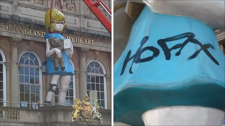 """Damien Hirst """"Charity"""" / spraypaint   (In 2011, this 22ft-tall outdoor statue was tagged with graffiti while on display at the Royal West of England Academy of Art. The tag, which read """"Hoax,"""" was subsequently removed.)"""