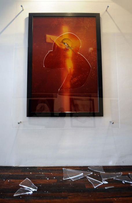 "Andres Serrano ""Piss Christ"" / hammer   (This controversial 1987 photograph has been attacked on multiple occasions - most recently in 2011, when a man smashed the work with the hammer while the piece was on view at Collection Lambert in Avignon, France. According to museum guards, a group of men arrived at the gallery at closing time. Two of them attempted to smuggle cans of paint spray and a chisel in their jackets. The guard noticed and proceeded to confiscate the objects - during which a third man took a hammer (or icepick or screwdriver, it remains unclear) to Serrano's piece. The attacker struggled with the guard, but helped by one of his accomplices, managed to escape. In the struggle, another Serrano work, ""The Church (Sister Jeanne-Myriam),"" was also damaged.   ""Piss Christ"" had been previously vandalized in 1997 (twice). The attacks took place within days of each other, while the work was on view at the National Gallery of Victoria, Australia. The first incident occurred when 51 year old John Allen Haywood took the photograph from the wall and kicked it. Haywood received a one month suspended jail term. He later told the press, ""You can go so far with taking the piss, you understand….It riles me, it really gets me very upset."" Asked what he would say to Serrano, he replied""I wouldn't like to say nothing to him. I'd just like to punch him on the nose."" Haywood's actions caused slight damage to the photograph's framing, but none to the work itself.   The very next day, two male teenagers also attacked the piece. According to witnesses, one teenager acted as a decoy, kicking a print on the opposite wall to distract museum guards. As the guards rushed to subdue him, the other teenager attacked  Piss Christ  with a hammer. Both teens were arrested; the print was damaged beyond repair.   In 2007, a group of neo-Nazis attacked a Serrano show in Sweden, although  Piss Christ  was not on display there.)"