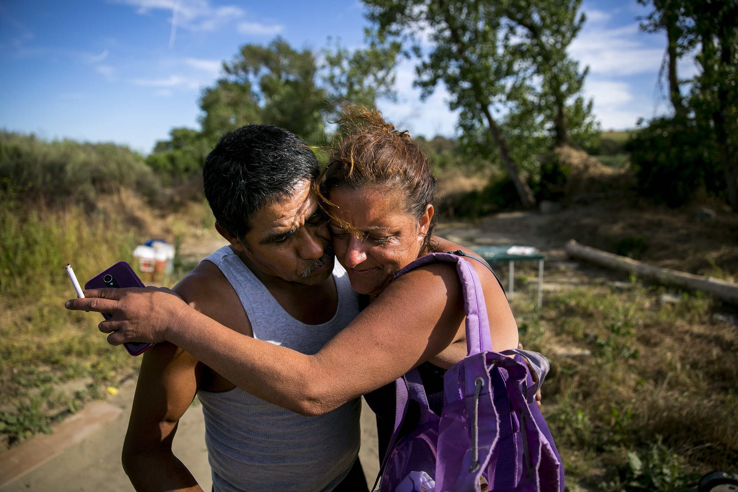 Coulter greets her friend Daniel Estrada, who she wound up staying with in the encampment later that evening, as she moves her belongings to the river bed.