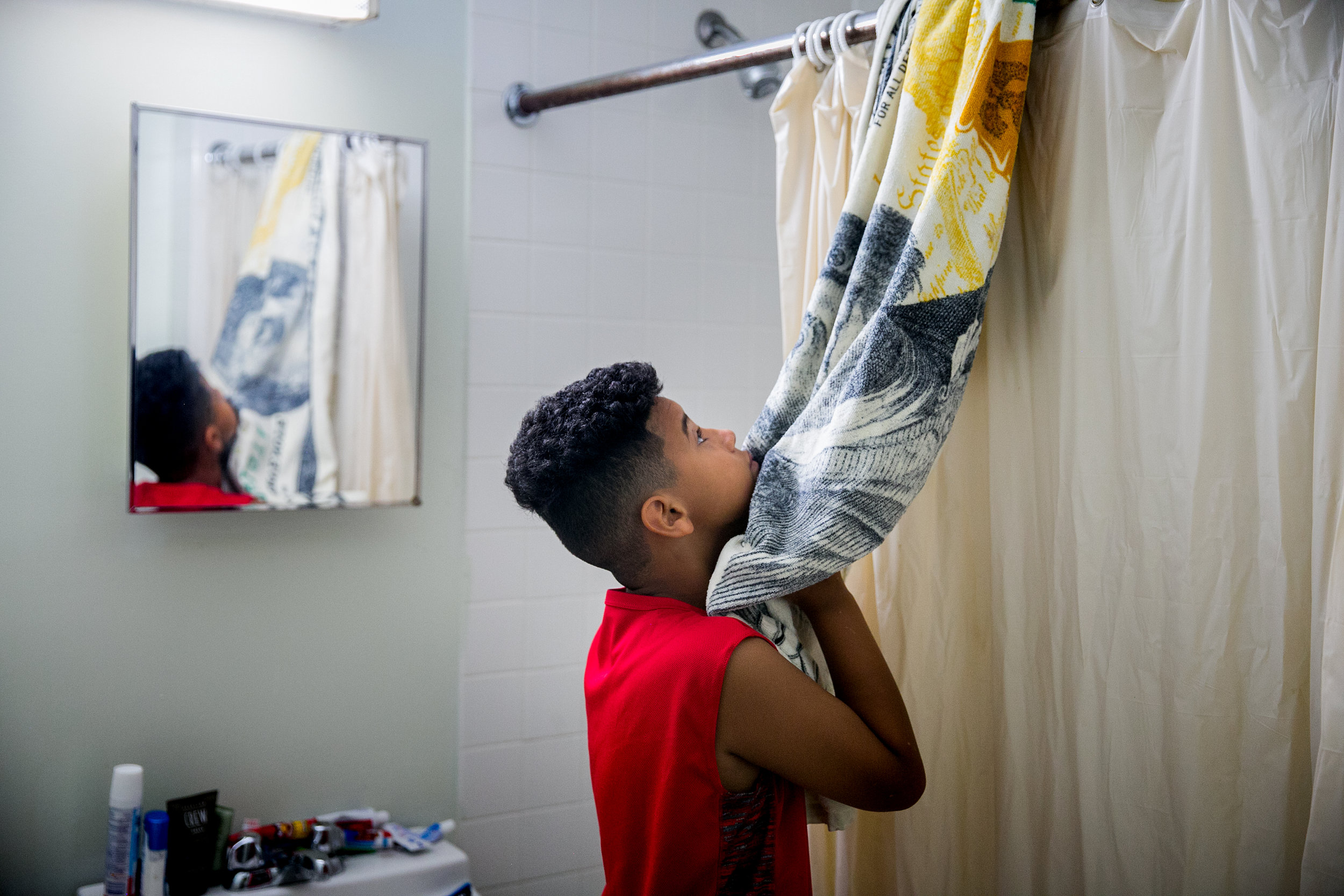 Pedro Cordero Jr. prepares for his day inside the room he shares with his father Pedro Cordero at a homeless shelter in Brooklyn, New York