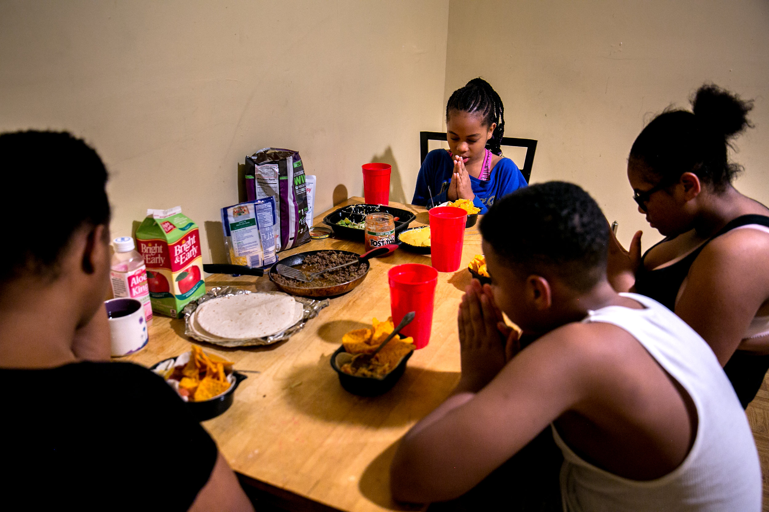 Shantae Young and her children Julian, Shaira and Shayla, say grace before eating dinner inside the shelter they're living in temporarily in the Bronx, New York.