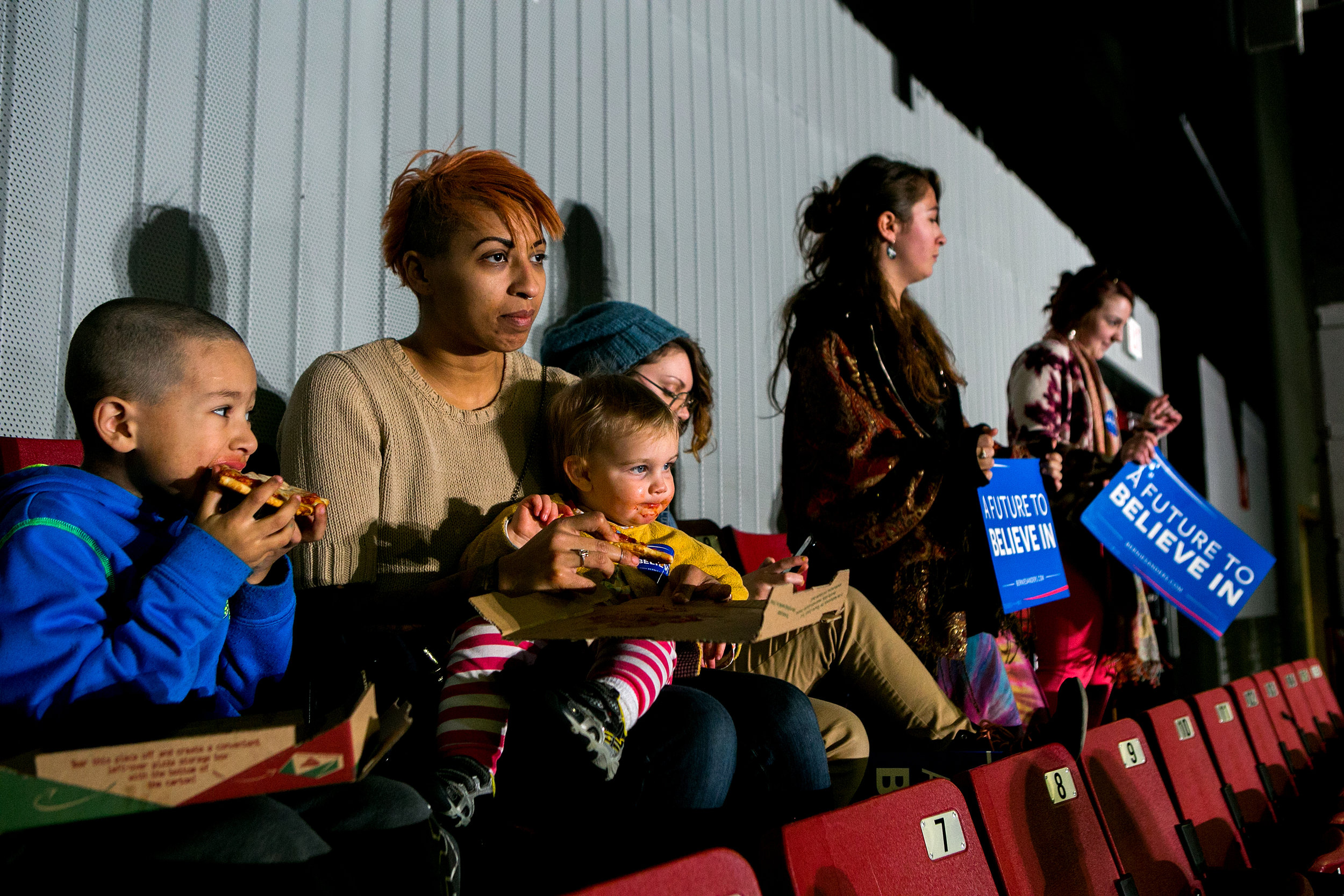 Alexis Parent feeds pizza to her friend's son as they wait for Bernie to speak at a rally in Amherst, Massachusetts.