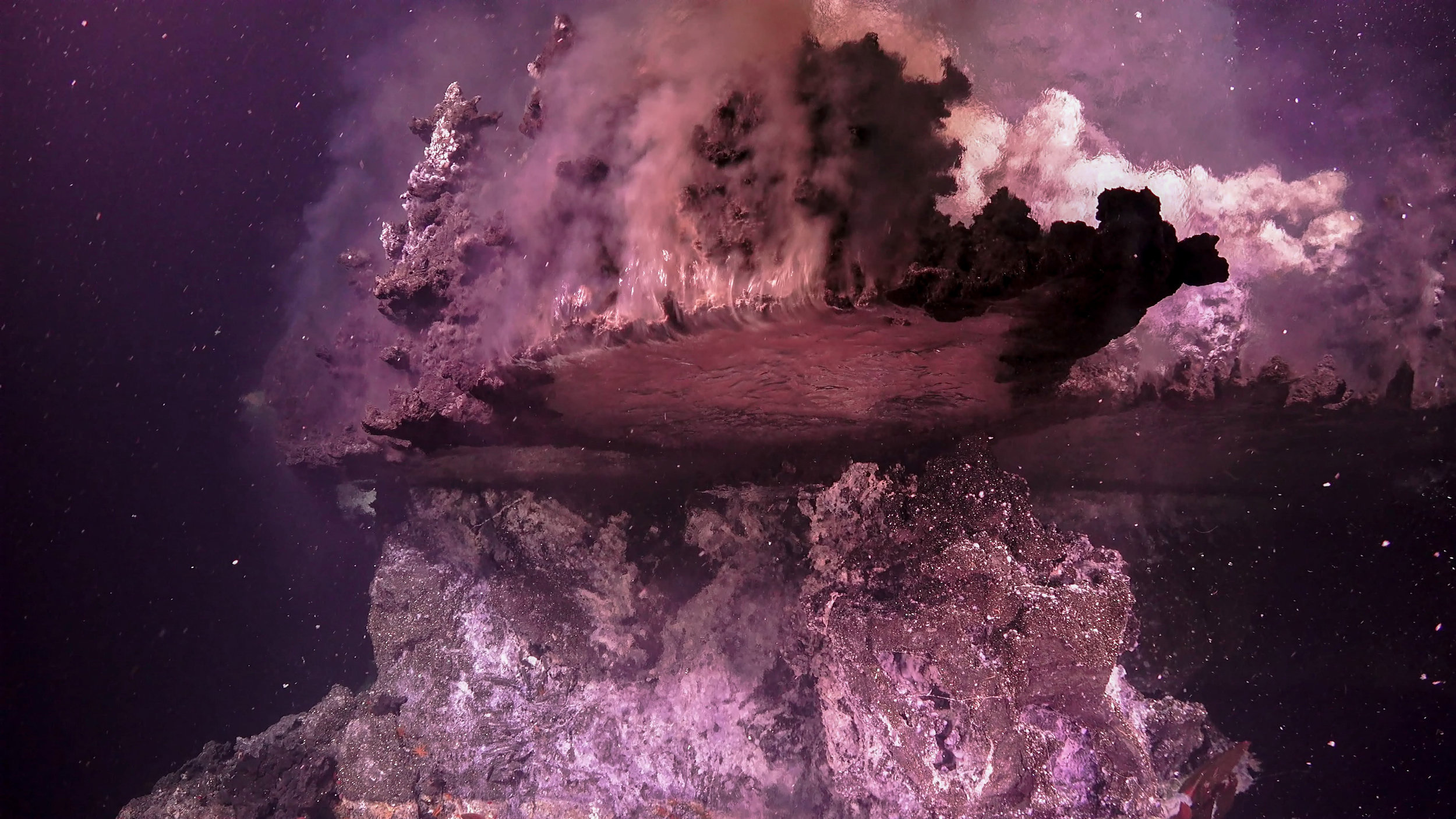 A broken hydrothermal vent flange gushing hot fluid over the side.  (Image courtesy of Schmidt Ocean Institute)