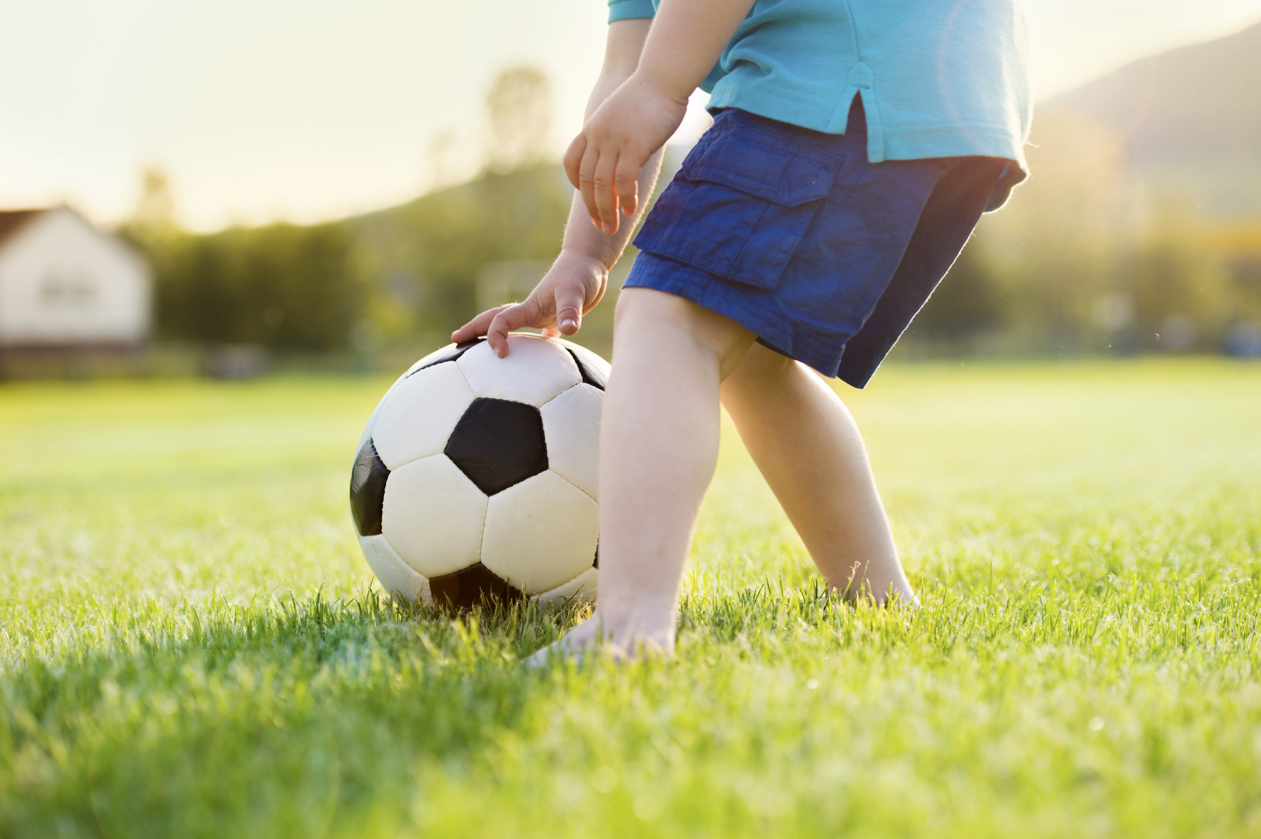 graphicstock-close-up-of-little-boy-playing-football-on-football-pitch_H0DW-X3bW.jpg