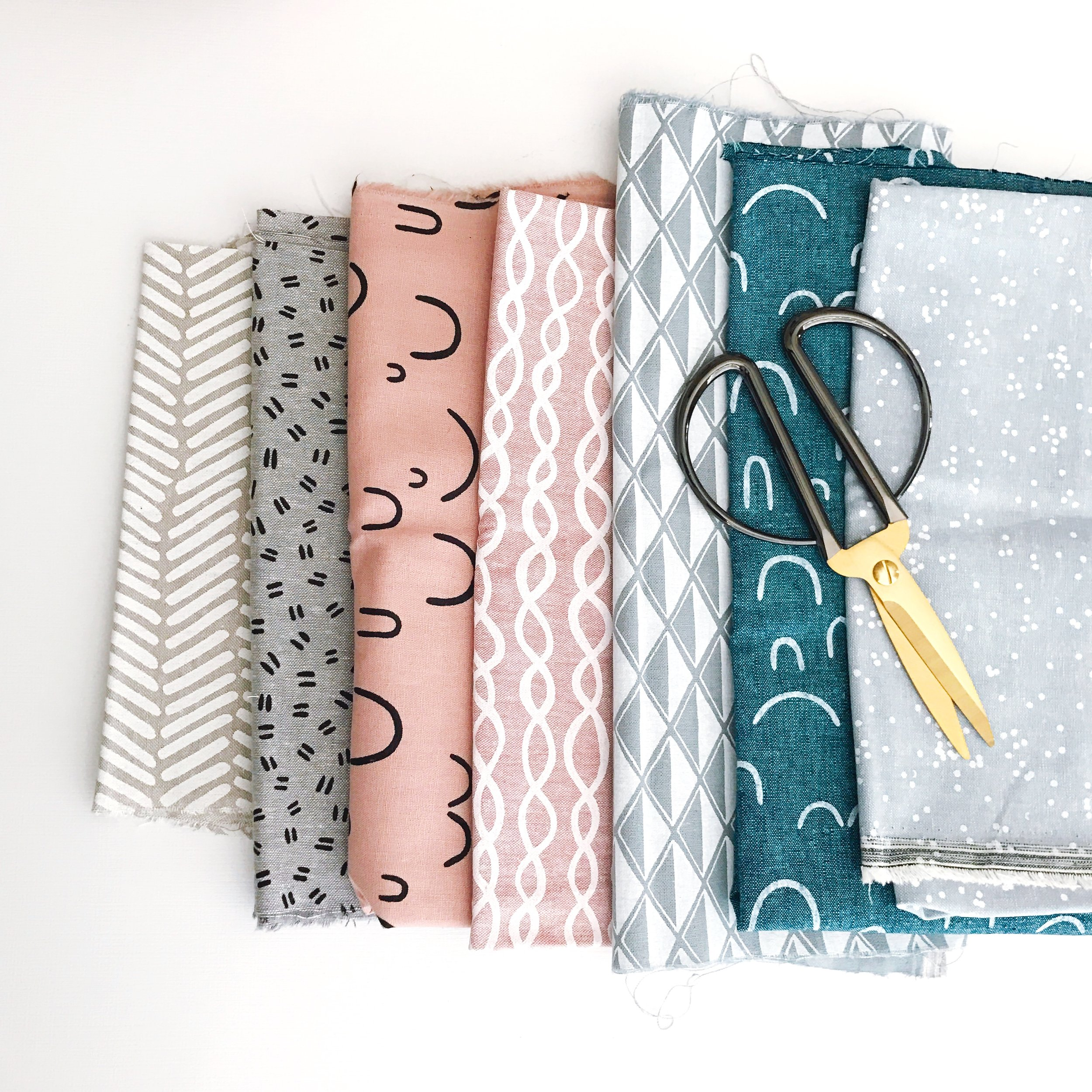 a line of folded fabric with a pair of scissors.